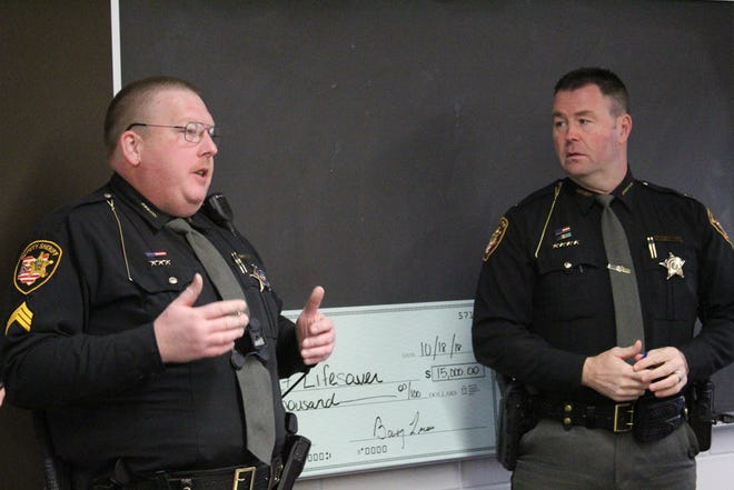Sandusky County Sheriff's Office Sergeant Eric Arquette, left, and Sheriff Chris Hilton explain Project Lifesaver, a new program to help find Sandusky County citizens who are prone to wander.