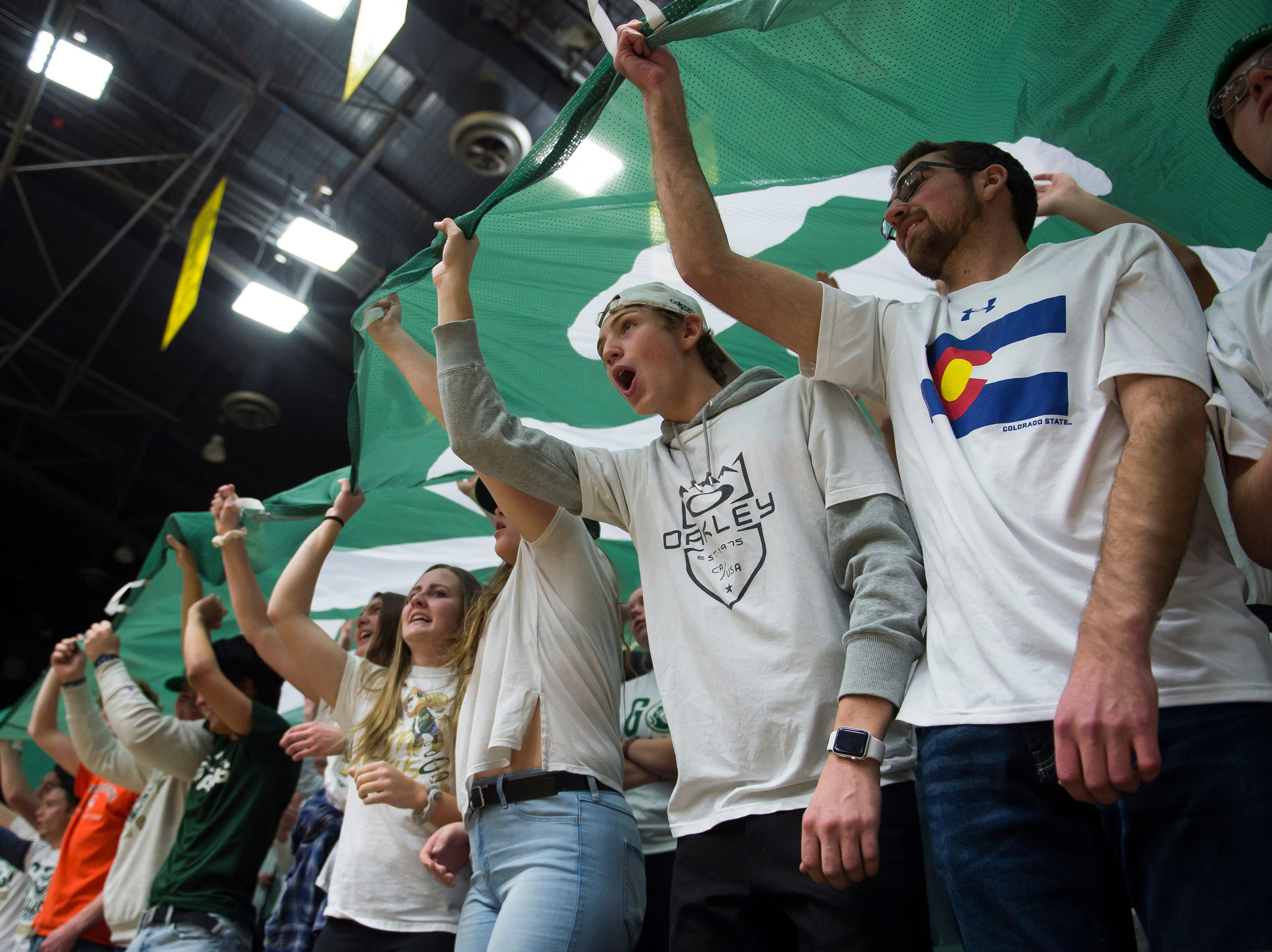 The Colorado State University student section holds a school flag over their heads before a game against Arkansas on Wednesday, Dec. 5, 2018, Moby Arena in Fort Collins, Colo.