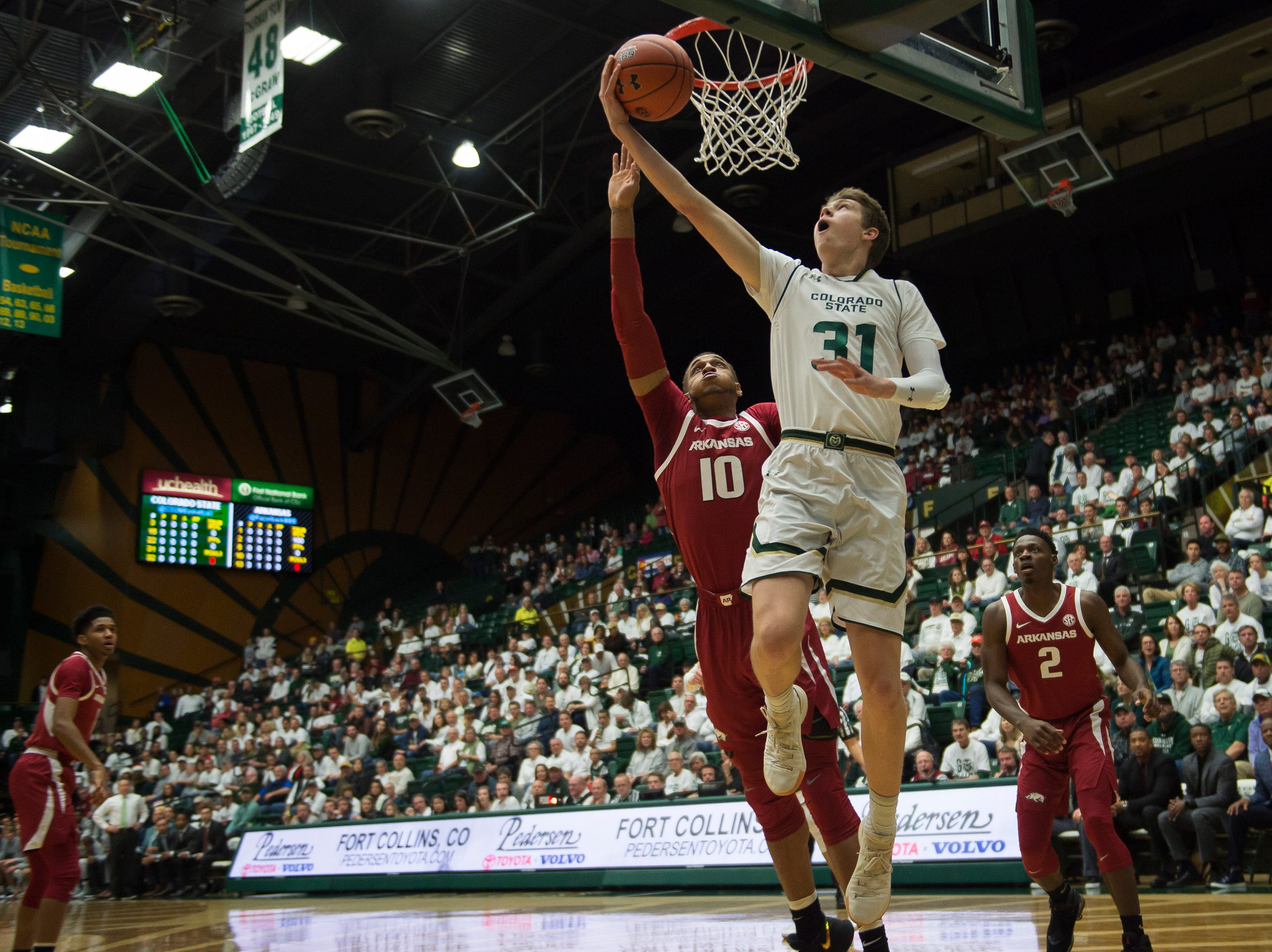Colorado State University freshman forward Adam Thistlewood (31) gets a layup past Arkansas sophomore forward Daniel Gafford (10) on Wednesday, Dec. 5, 2018, Moby Arena in Fort Collins, Colo.
