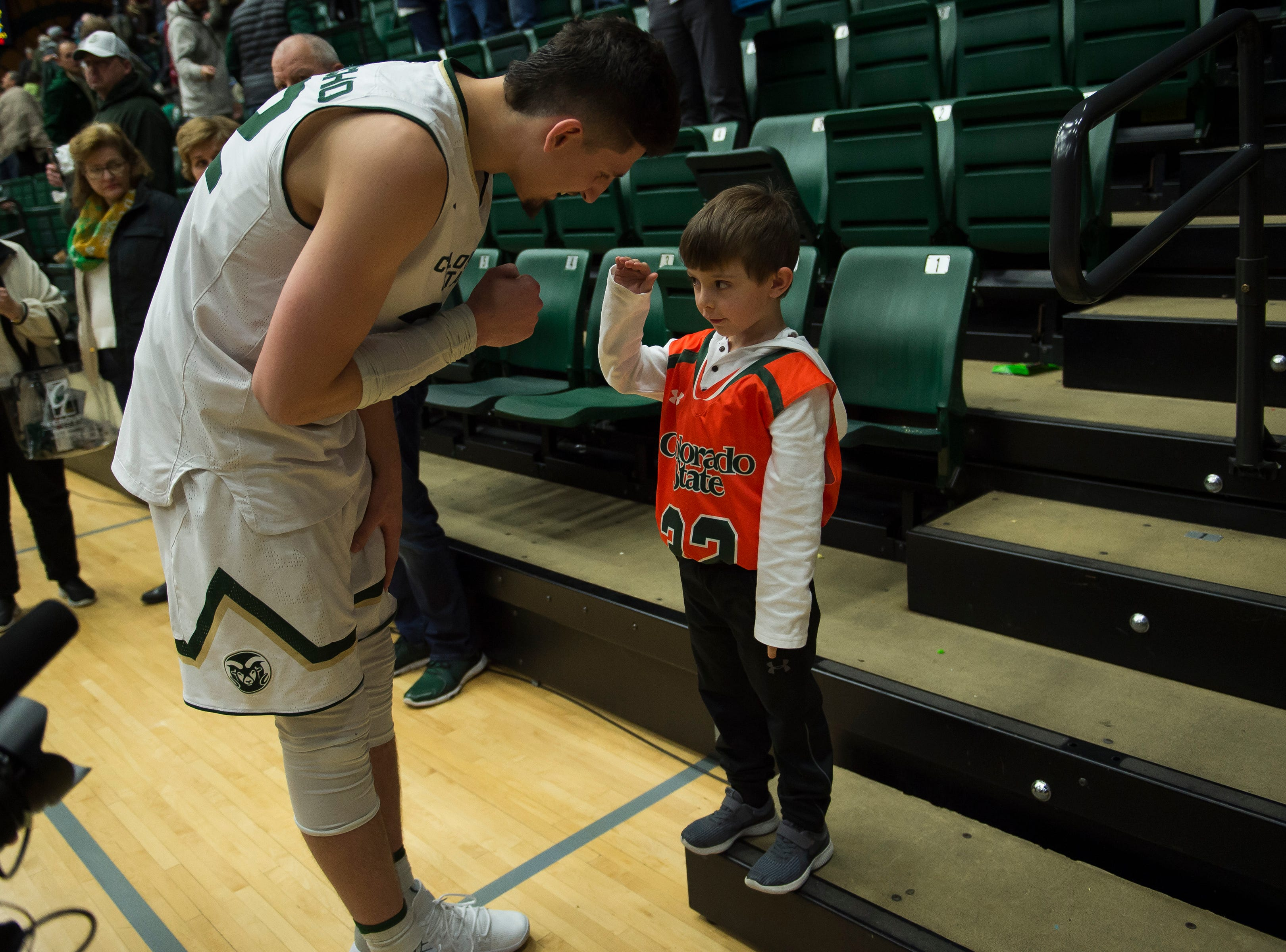 Colorado State University junior center Nico Carvacho (32) greets a young fan after a game against Arkansas on Wednesday, Dec. 5, 2018, Moby Arena in Fort Collins, Colo.
