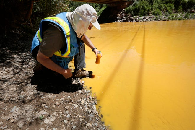 FILE - In this Aug. 6, 2015, file photo, Dan Bender of the La Plata County Sheriff's Office takes a water sample from the Animas River near Durango, Colo., after the accidental release of an estimated 3 million gallons of waste from the Gold King Mine. The EPA said Friday, Nov. 30, 2018, that fish and other aquatic life didn't suffer severe or long-lasting damage from the spill. The EPA says part of the Animas River in Colorado closest to the spill were already so polluted by decades of waste spilling from inactive mines that the most vulnerable fish, insects and other aquatic life were already gone.  (Jerry McBride/The Durango Herald via AP)