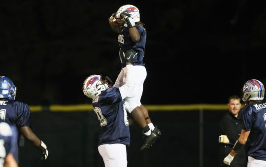 Riverdale High School's Tre Dickerson and Quantavius Brown, top, celebrate Brown's touchdown against the South team during the Rotary South All-Star Classic on Wednesday in Fort Myers.