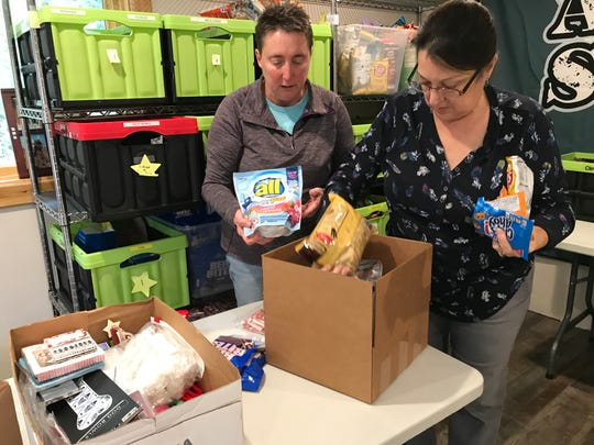 Adopt-a-Soldier founder, Nancy Hutchinson, puts supplies on a table where volunteer Debby Brzinski fills boxes.