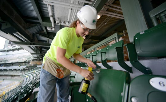 Ashley Raeder of Green Bay installs number plates to new seats in the south end zone of Lambeau Field in 2014. She is a graduate of the Transportation Alliance for New Solutions program.
