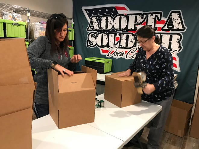 Ashley Bittorf, left, and Debby Brzinski, pack boxes for Adopt-a-Soldier Thursday, Dec. 6, 2018.
