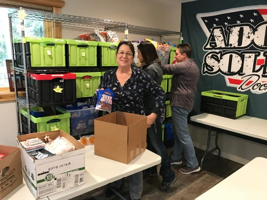 Volunteer Debby Brzinski puts packages of food in to a box. Volunteer Ashley Bittorf and Adopt-a-Soldier founder Nancy Hutchinson gather supplies for boxes.