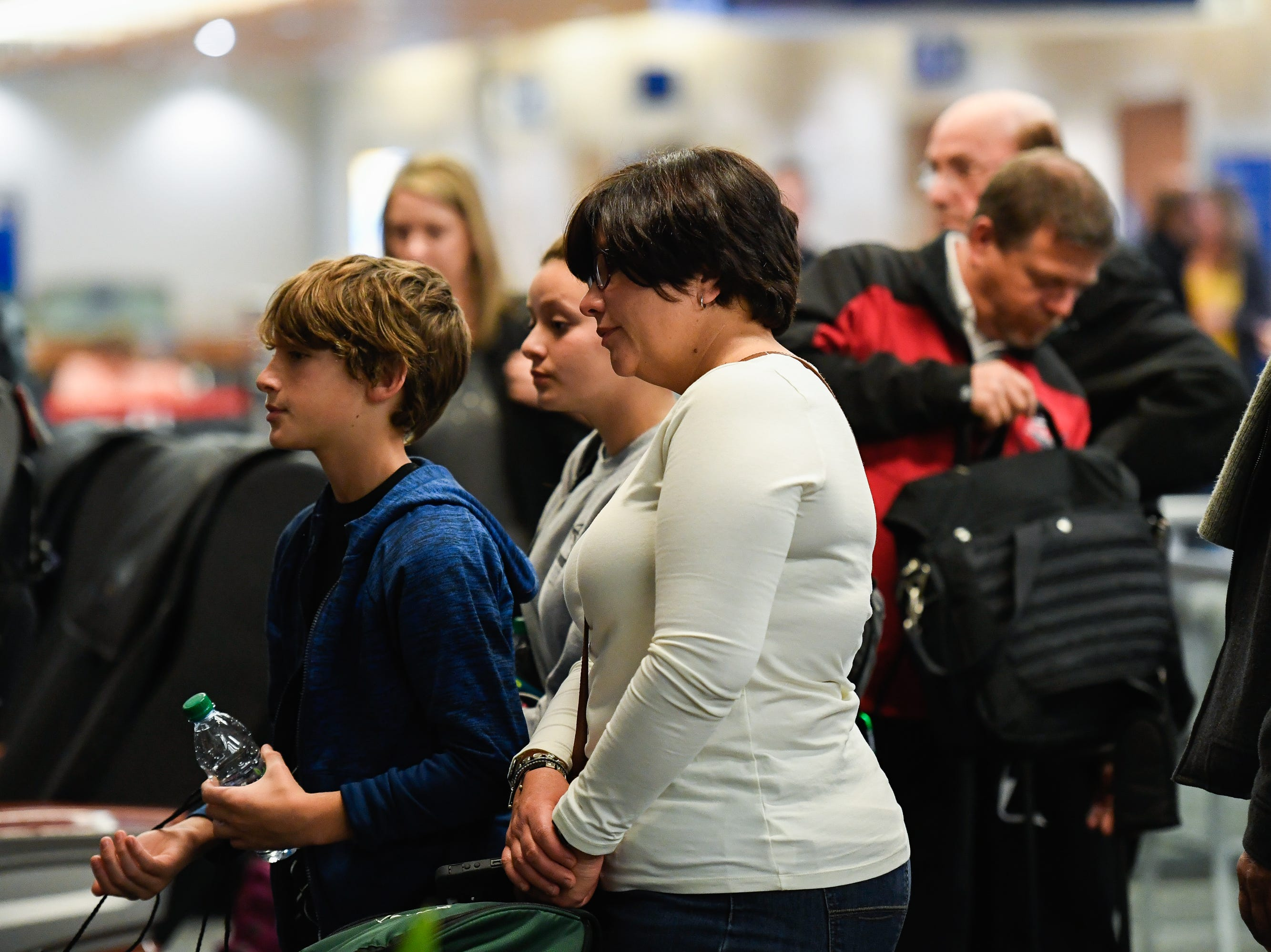 Spectators watch as U.S. Navy Fireman 2nd Class Carl Dorr is escorted off a Delta Airlines flight and brought home on Wednesday, Dec. 5, 2018.