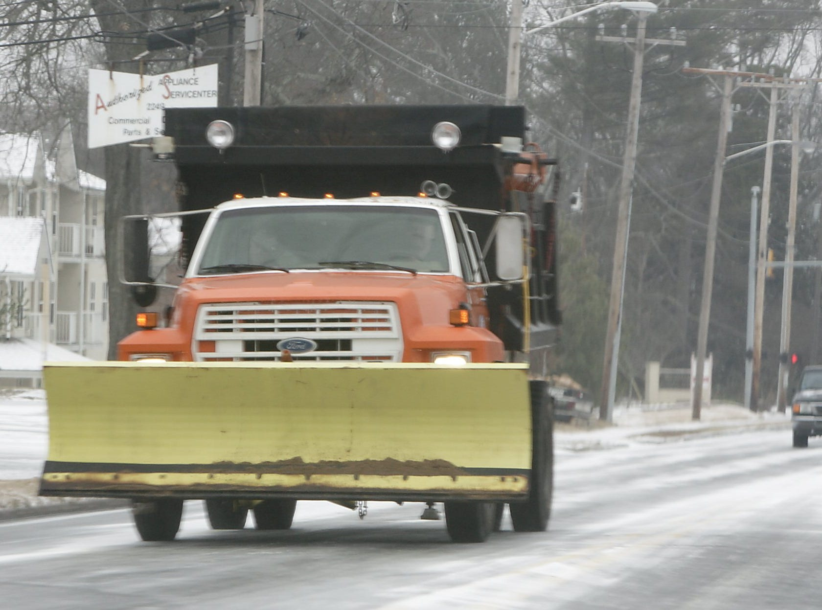 A snow plow travels Augusta Road in Greenville, Saturday, January 29, 2005.