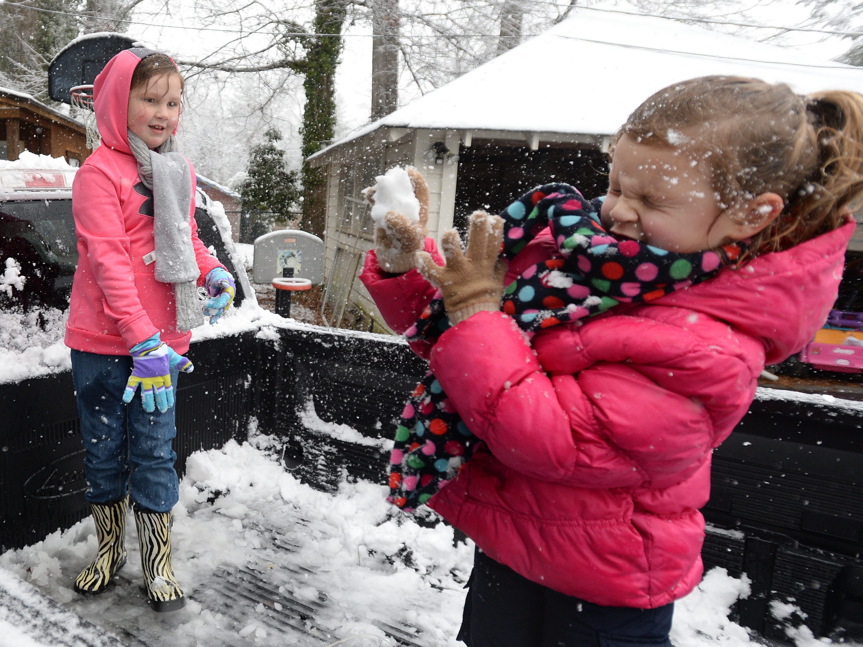 Eight-year-old Eva Kate Carwile throws a snow ball at her sister Addison, 4, in their yard in Belton Tuesday, February 11, 2014.