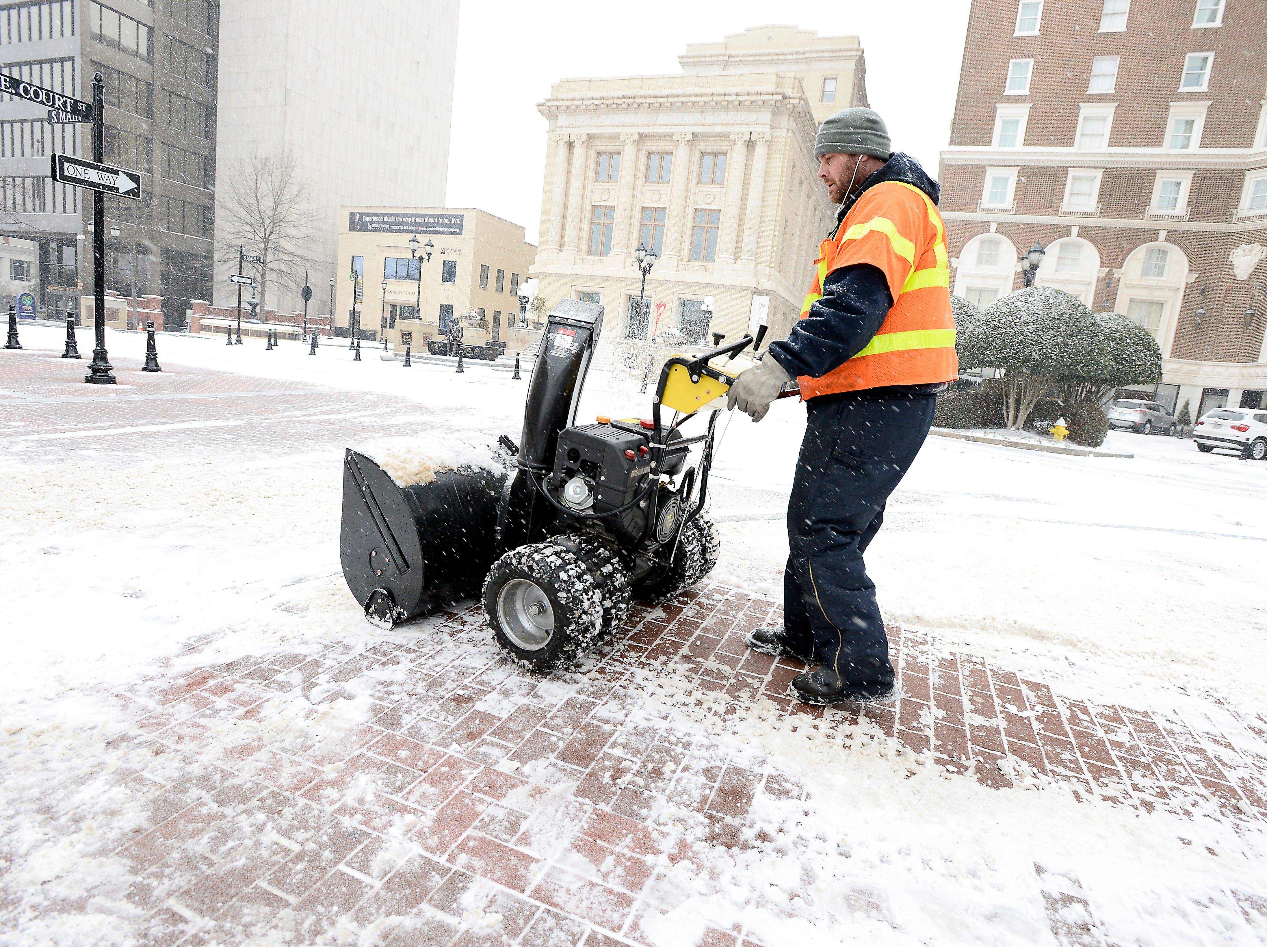 A City of Greenville worker uses a snow blower to remove snow from downtown sidewalks on Wednesday, February 12, 2014.