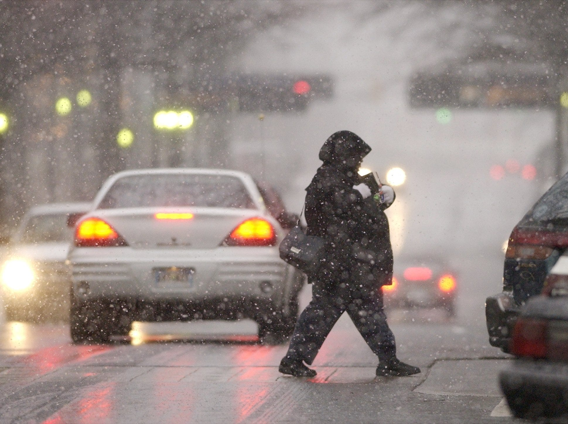 A pedestrian crosses Main St in downtown Greenville as snow falls Thursday January 16, 2003.
