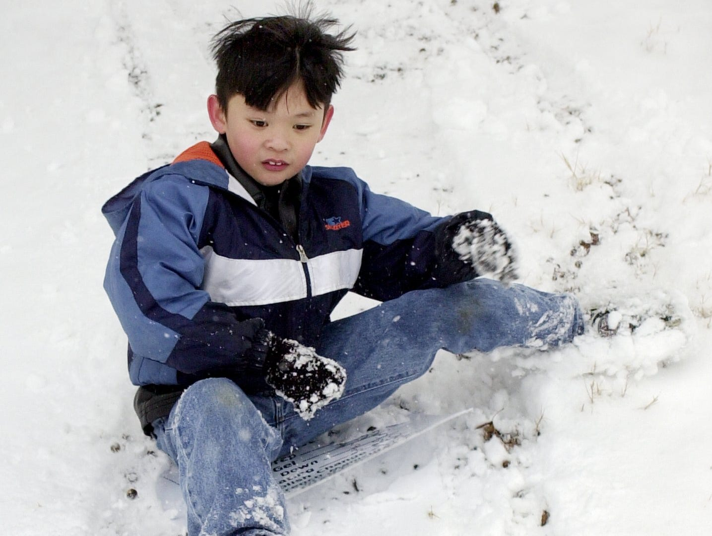 Kenny Doan , 8 slides down a hill near Palmetto Exposition Center l/3/02 using a plastic sign as his toboggan. He was playing in the snow with his sister and his uncle.