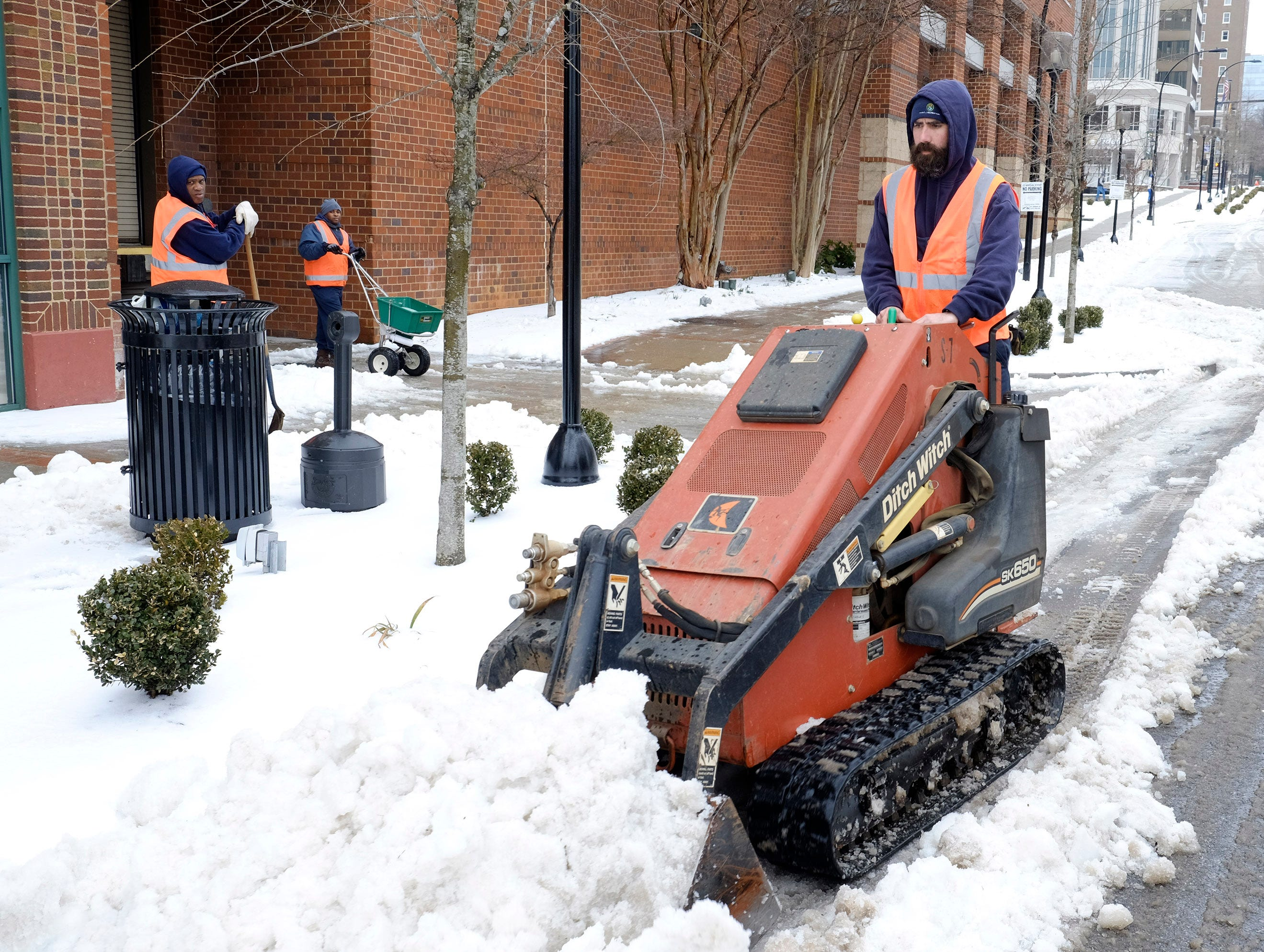 Workers clean up the snow on Main Street in Greenville Wednesday, February 12, 2014.