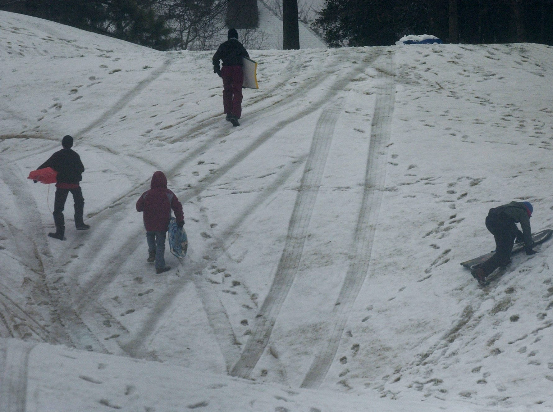 Children climb up a hill with sleds in the Thornblade subdivision on Thursday, February 1, 2007.