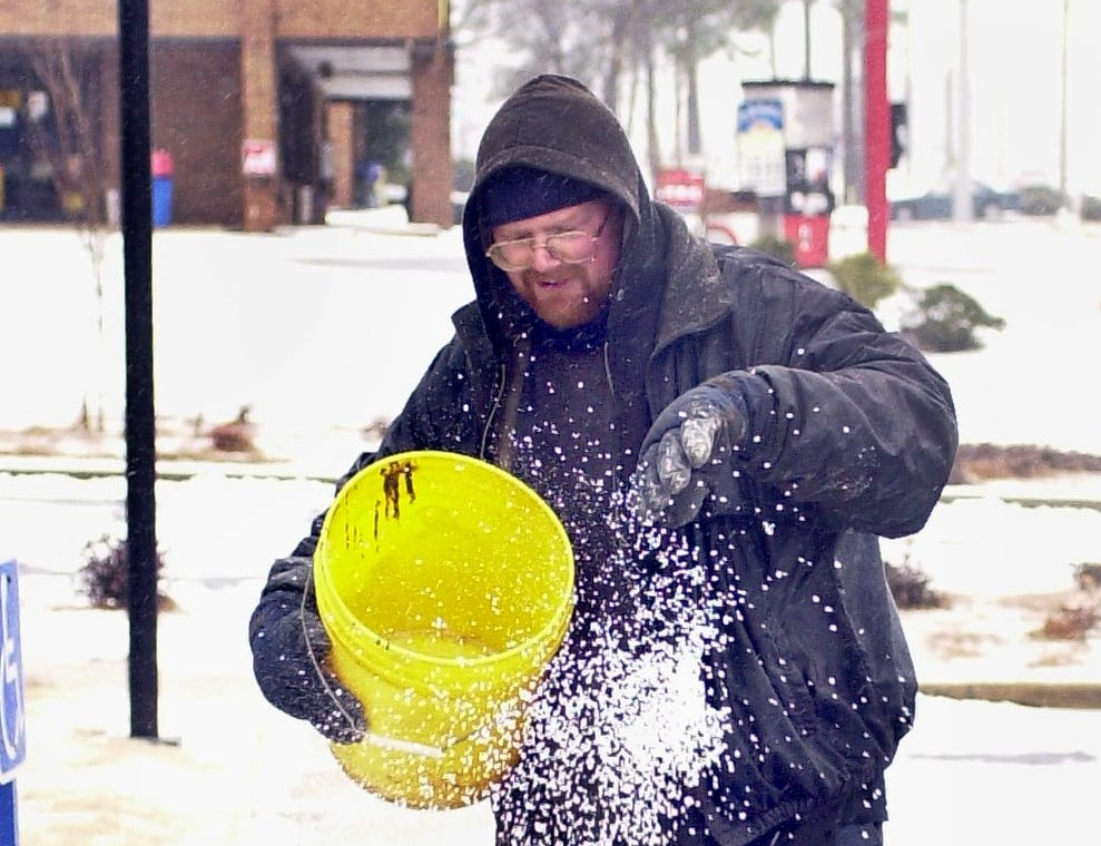 Richard Bower finishes spreading a bucket of de-icer on the walks of a Woodruff Rd. bank January 29, 2005.