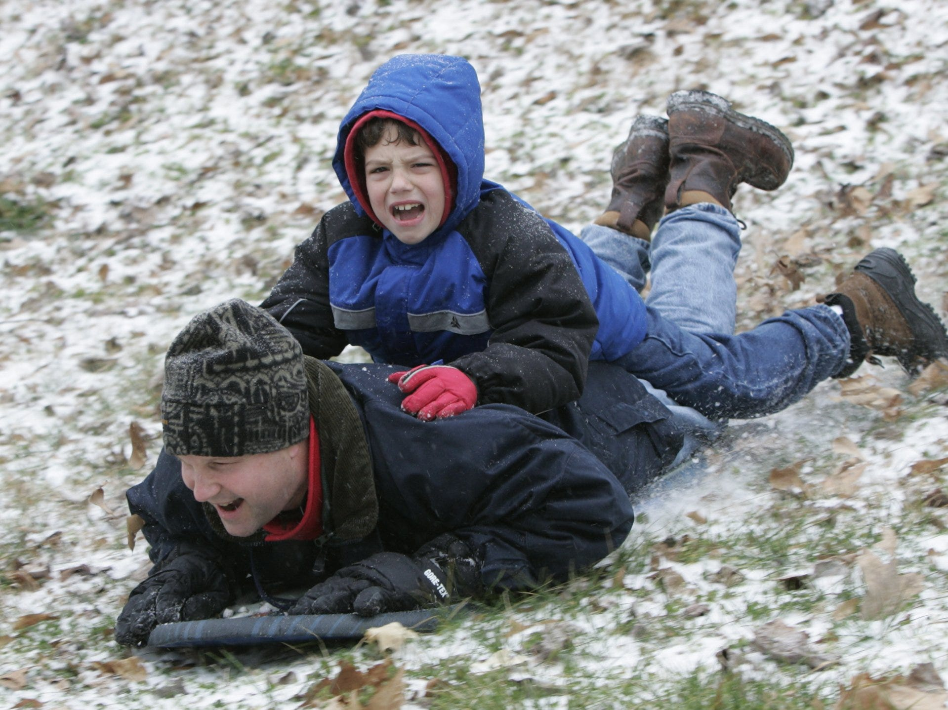 -Tom Baumgarter slides down a hill at Cleveland Park with his son, Christoper, lying on his back, Saturday, January 29, 2005.