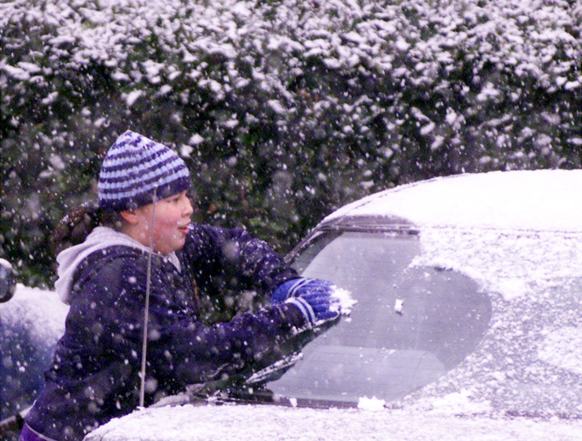 Jeimi Parra , ll makes a snowball from the snow on a car's rear window as she and others at Polo Club Apartments take advantage of the late afternoon snow January 16, 2003.