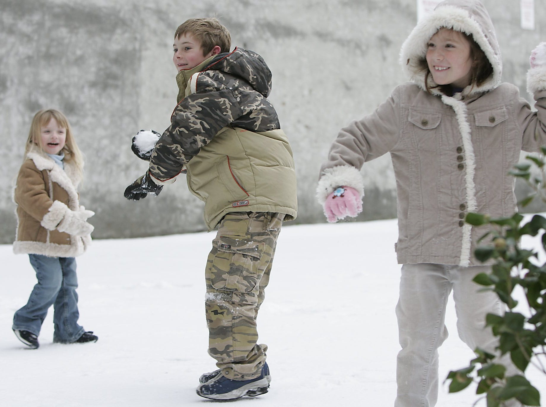 Macy Robert, 3, from left, Hunter Mixon, 8, and Samantha DuPree, 6, of Charleston, have a snowball fight with thier parents in downtown Greenville, Saturday, January 29, 2005.