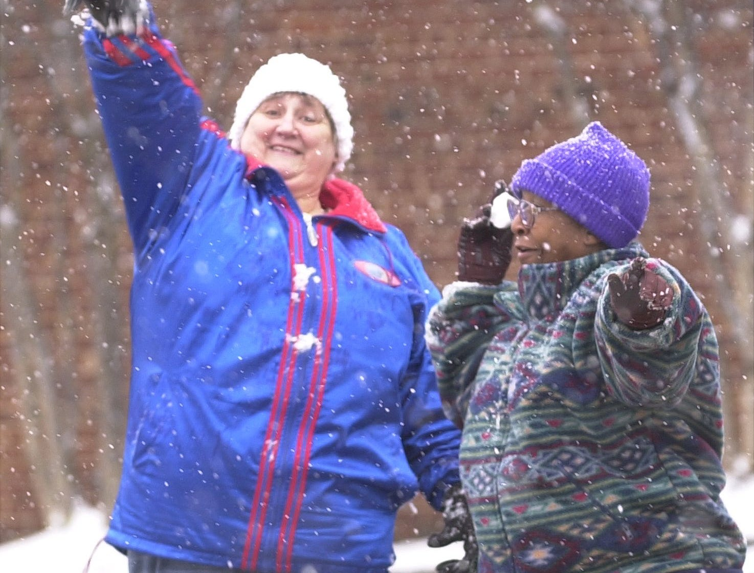 Joann McGowan (left) and Shirley Robinson (right) take advantage of the snow and throw snowballs along Richardson St. in downtown Greenville January, 3, 2002.