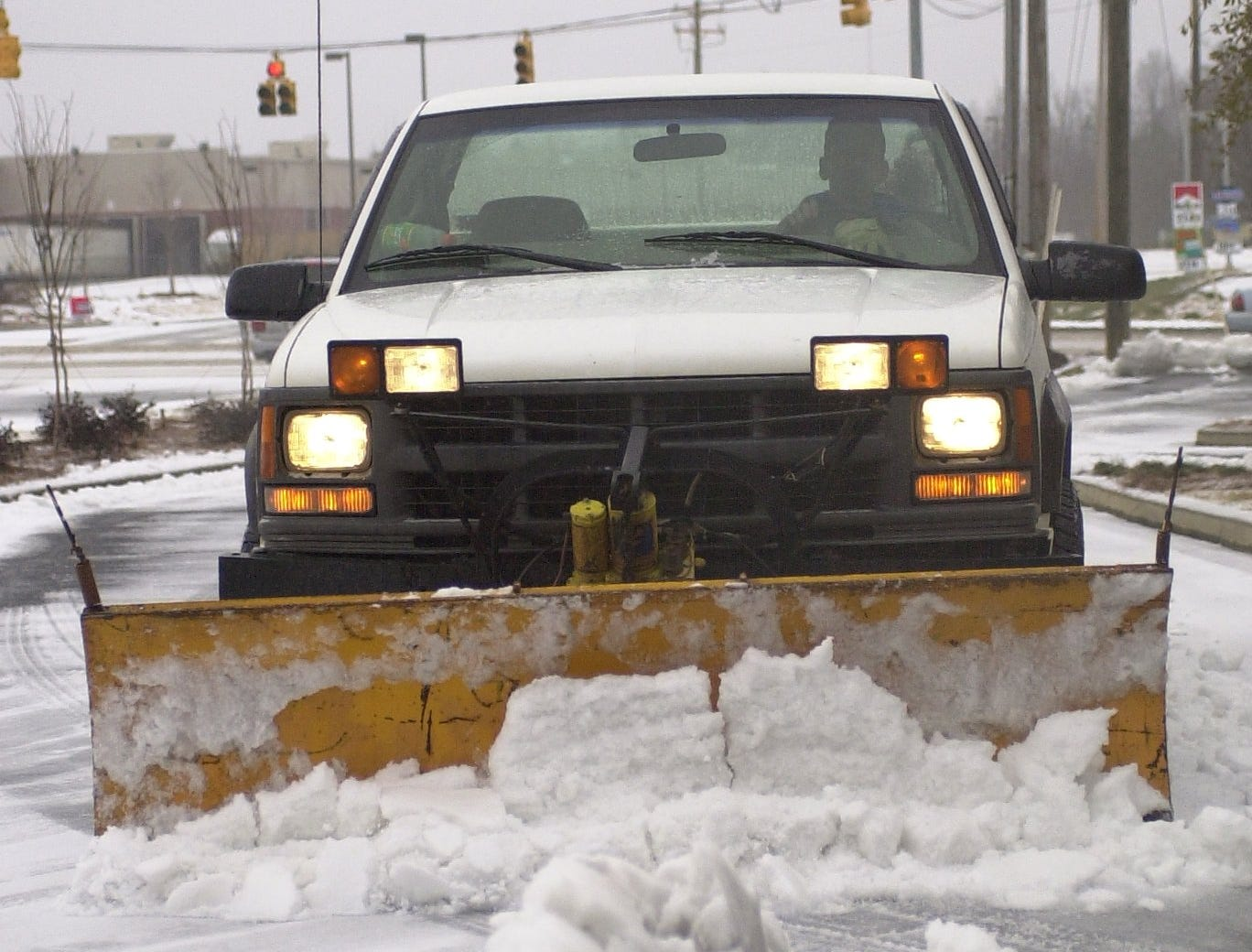 Chris D'Auria guides his pickup with snow a plow attached as he clears the snow and ice covered parking lot of a bank on Woodruff Rd January 29,2005.