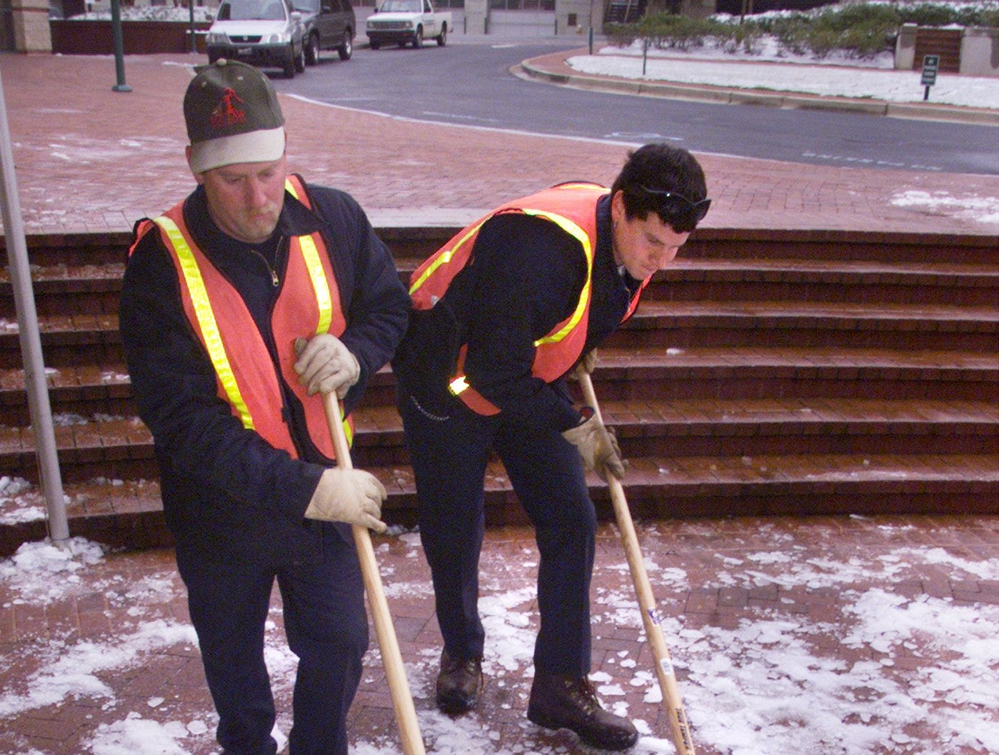 City of Greenville workers Brian Crenshaw, left, and Todd Pannell, right, scrape snow from the sidewalk outside the Peace Center in downtown Greenville Monday January 24, 2000. They were working with Peace Center employees to clear the area of dangerous ice.