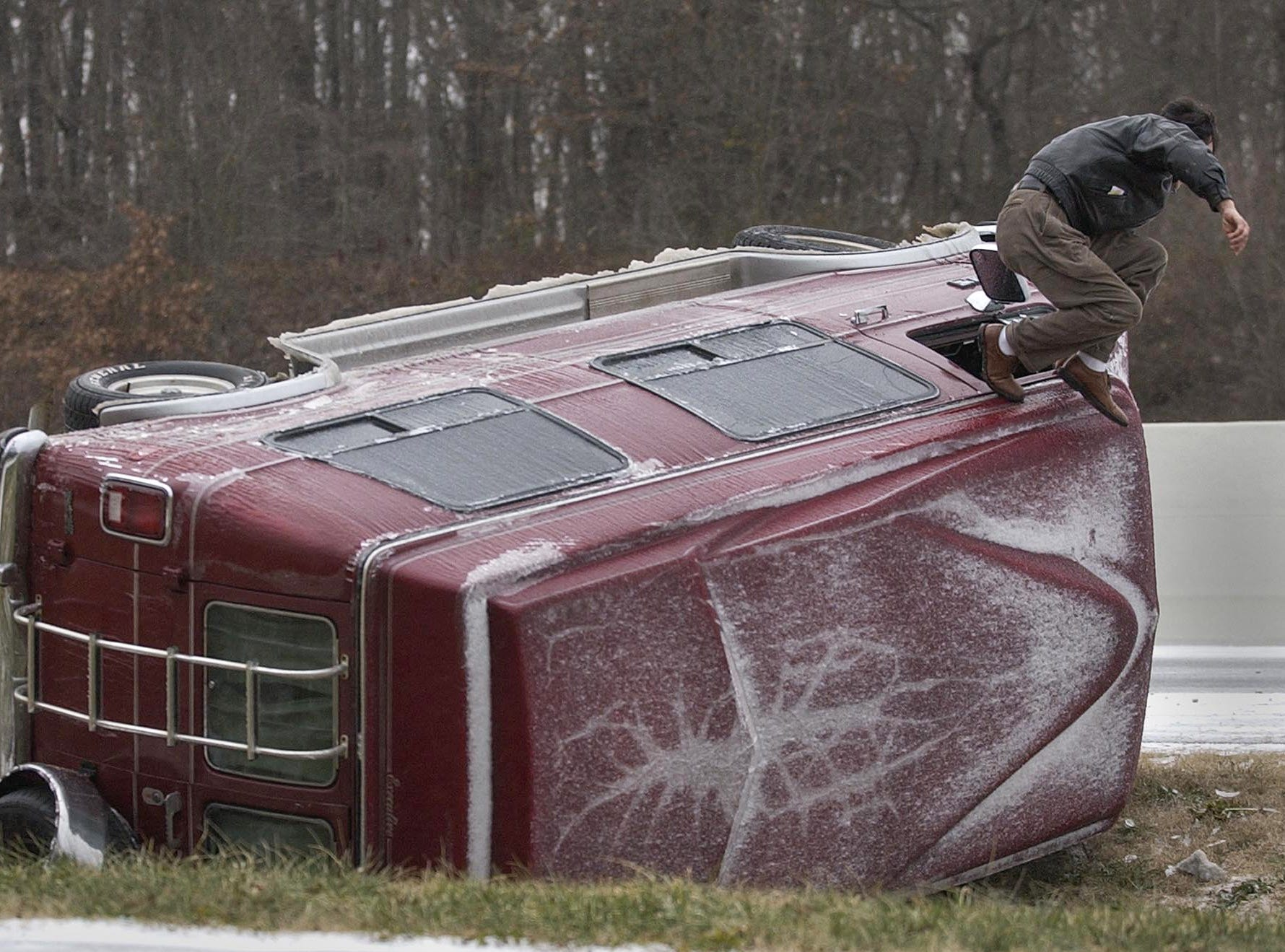 The driver of a van that overturned on I-85 near Hwy 8 in Anderson County jumps from the window Saturday January 29, 2005. The driver, who who is from Atlanta and would not ID himself, was not injured in the accident.