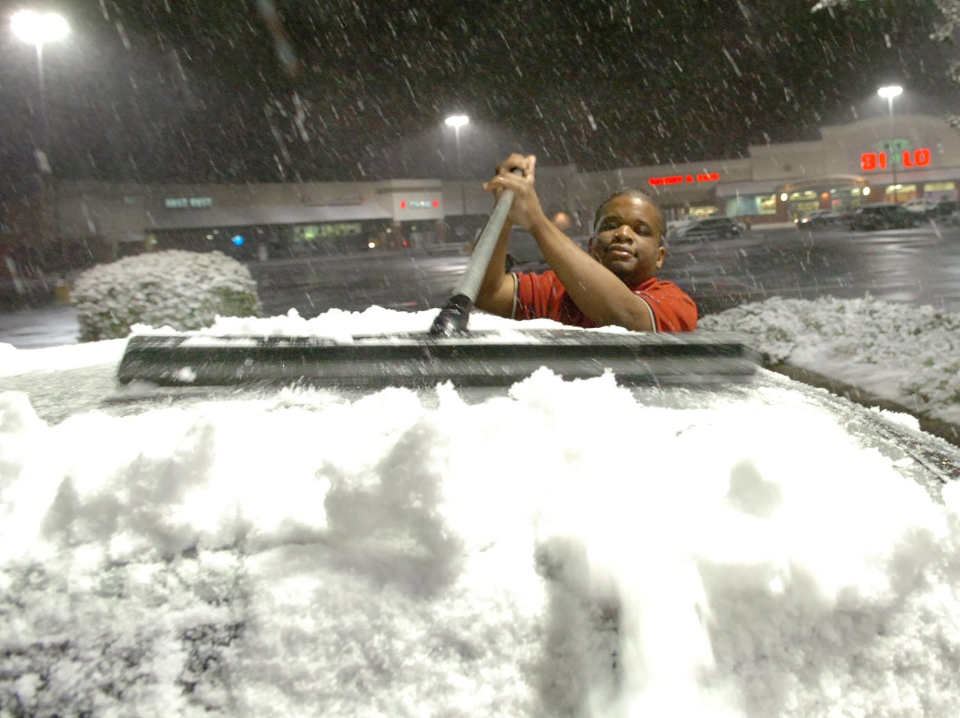 Jonathan, a Team Leader at the Burger King on Woodruff Road, sweeps the snow off of his car windshield around 10:30 Wednesday January 16, 2008.