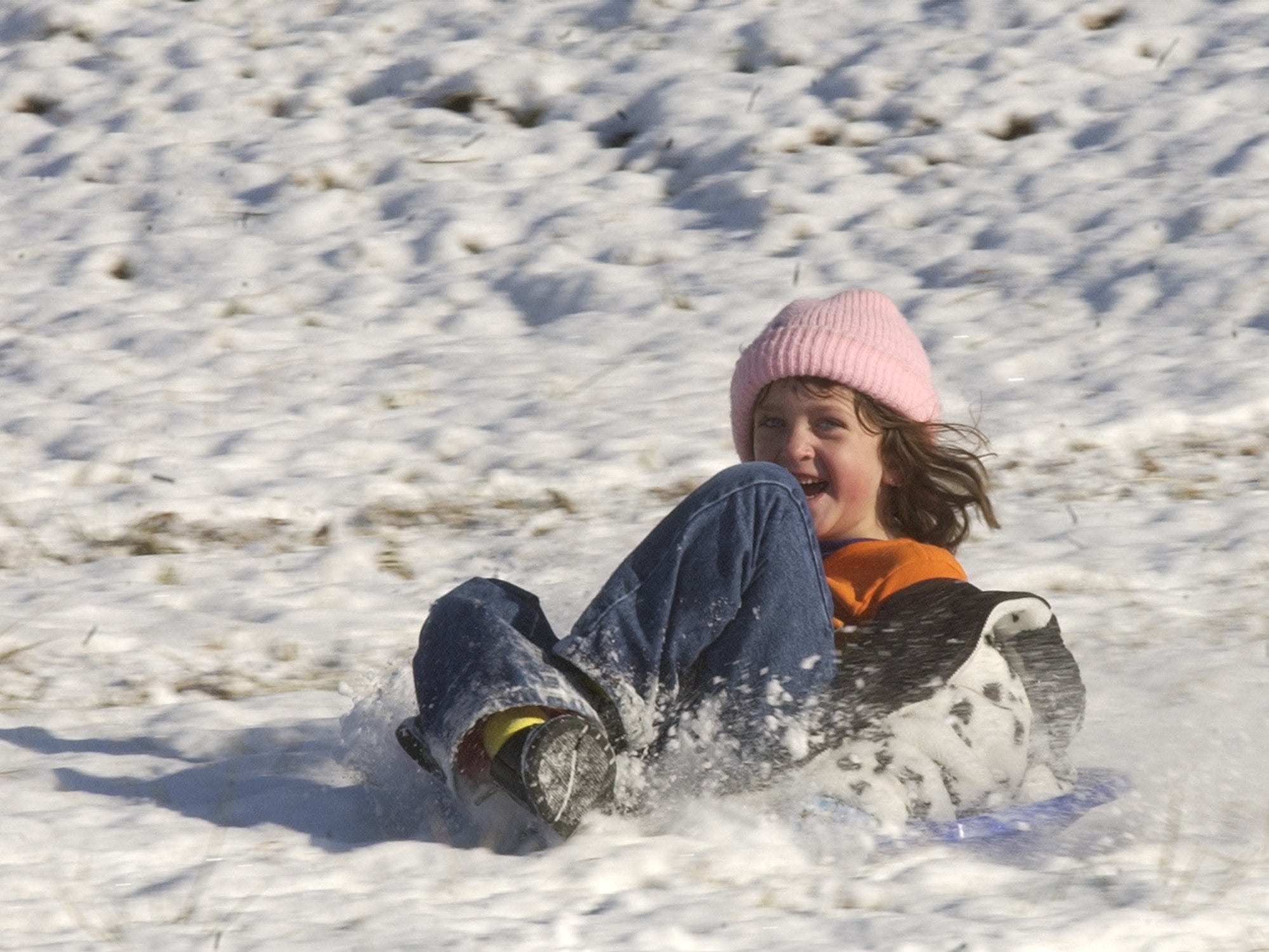 Stephany Baily slides down the hills covered with snow off West Parker in Berea January 17, 2003.