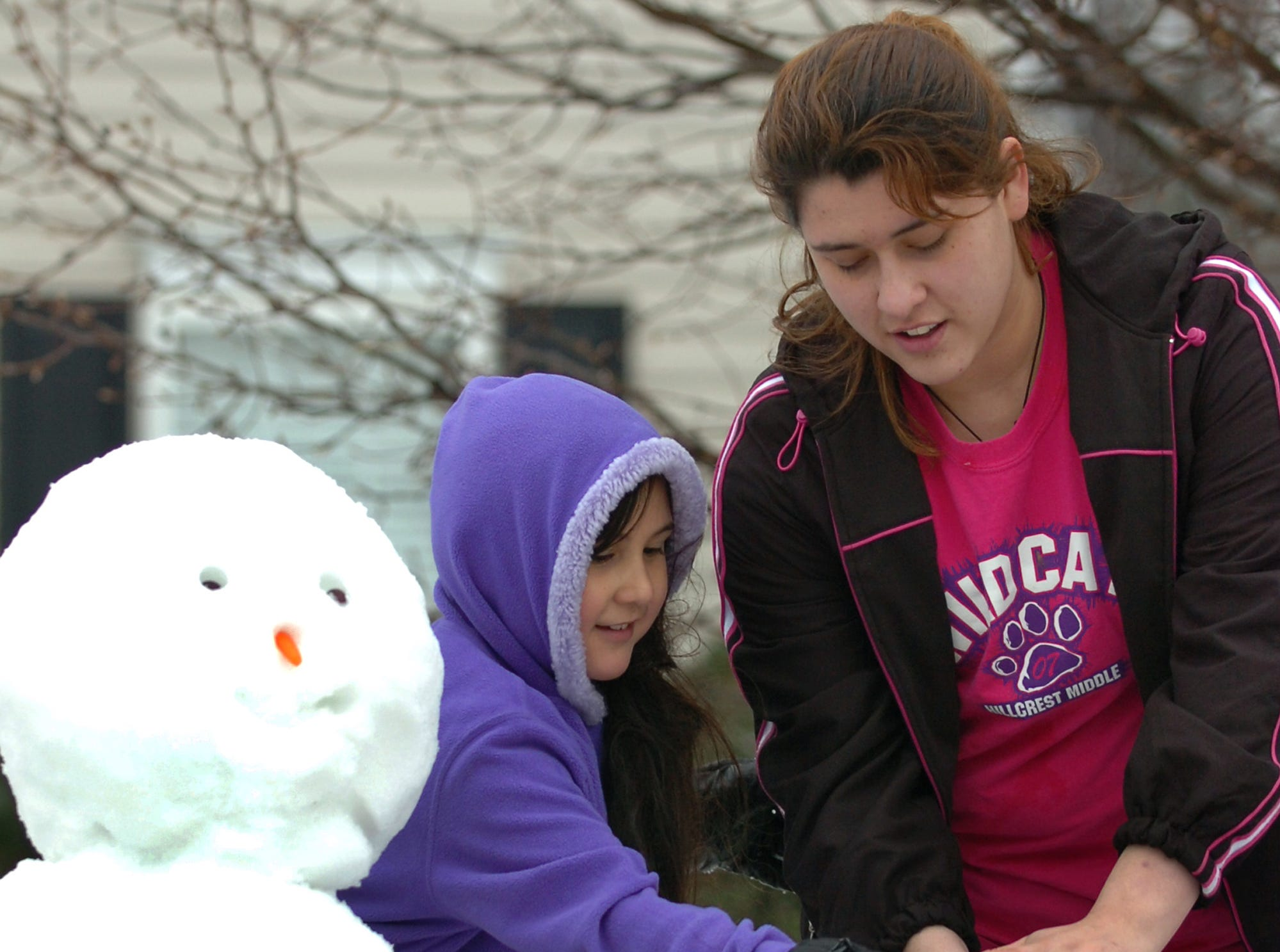 Elizabeth Vera, left, gets some help from her sister Stephanie as the family creates a snow family in the front yard of their Simpsonville home Thursday, February 1, 2007.