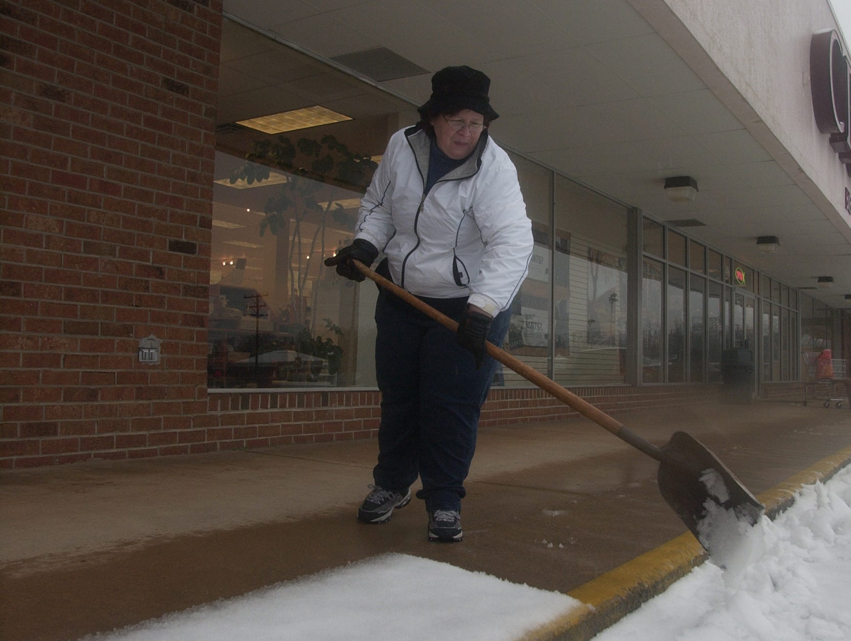 Terry Smith, a book-keeper at Cross Way, shovels in front of the East North Street store on Thursday, February 1, 2007.