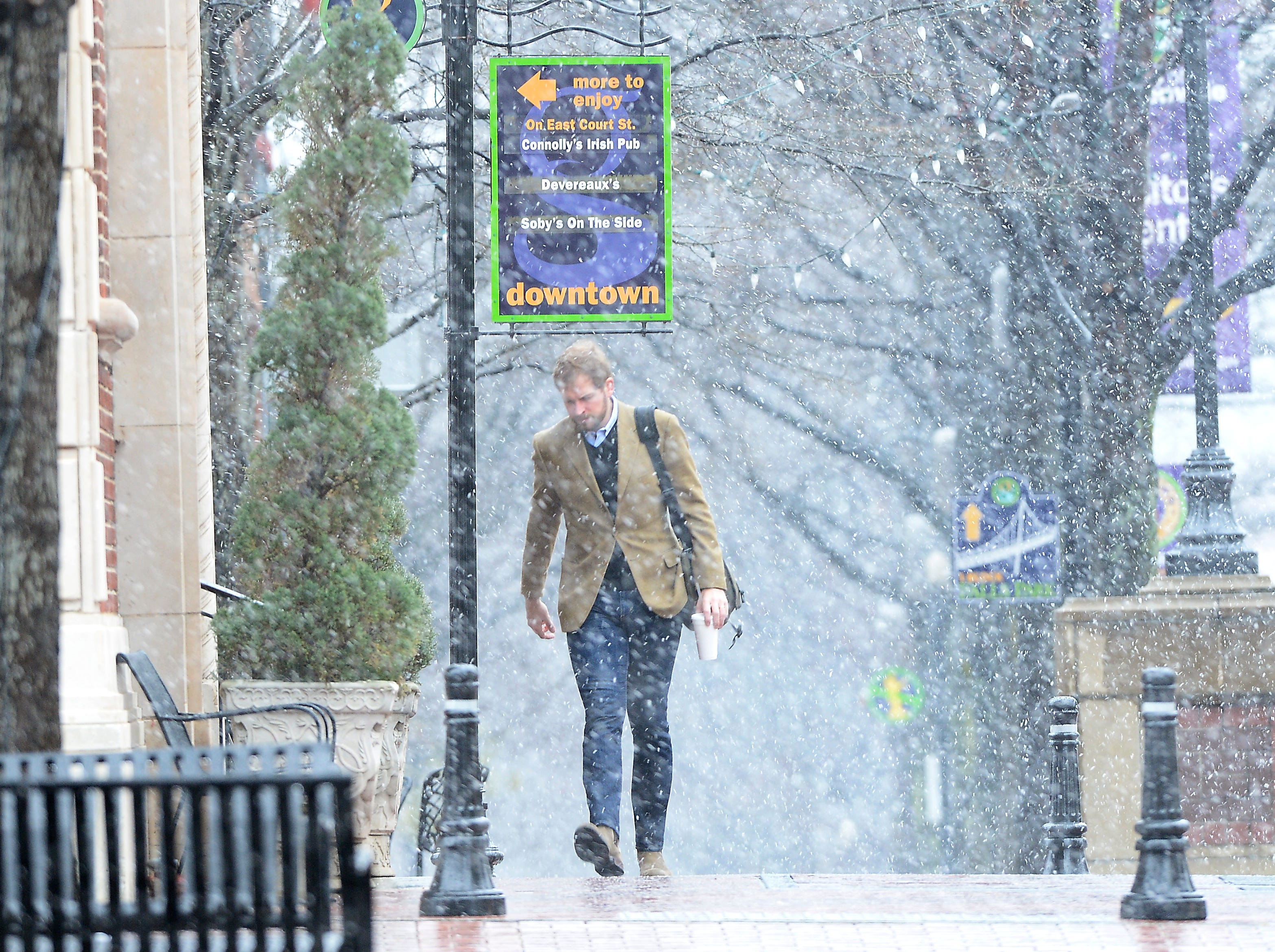 With snow fall picking up, Upstate residents make their way down Main Street on Tuesday, February 11, 2014.