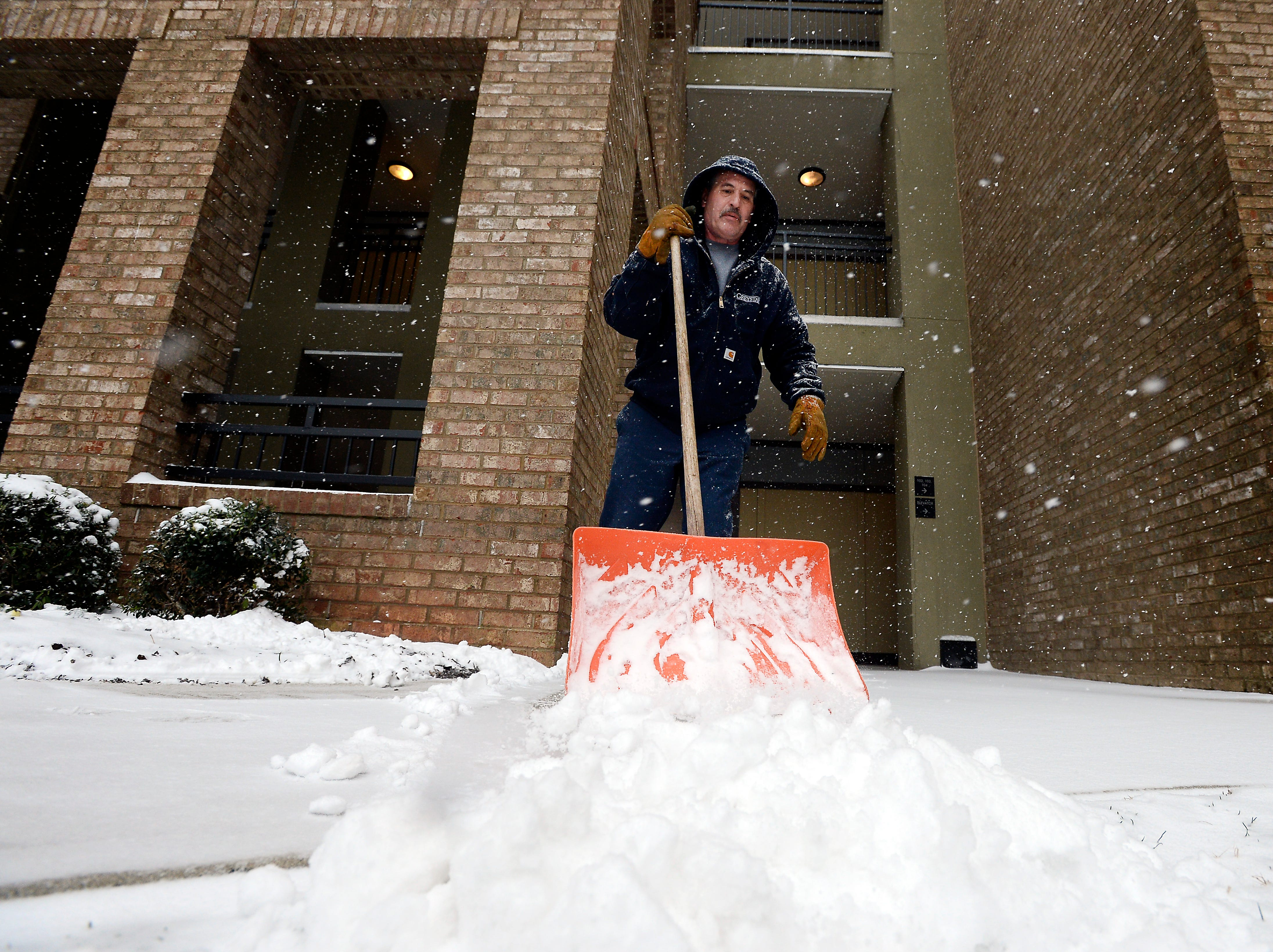 David Somerville, maintenance supervisor at McBee Station, shovels snow from the apartment sidewalks on Wednesday, February 12, 2014. somerville