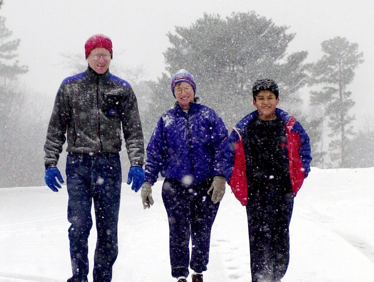 Don , Barb, and Jonathan Pierce (left to right) led by their dog ,Skip make their way along a snow covered S. Parker Rd January 3, 2002.