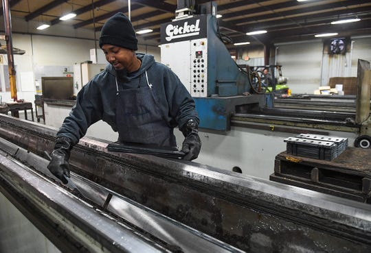 Rashad Hester places blades on a grinder at Knife Source in Ft. Inn Thursday, December 4, 2018.