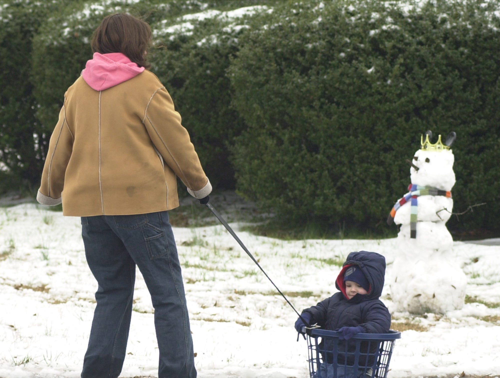 Teresa Perry pulls her son Jake in a laundry basket up their Easley driveway Thursday, February 1, 2007.