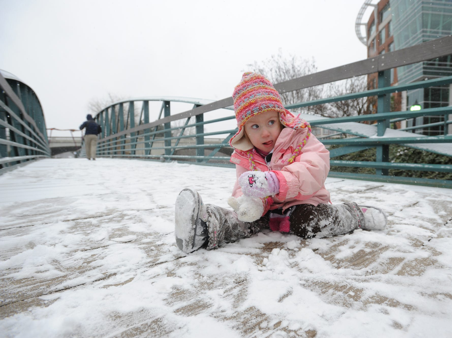 Lucy Baker looks in the direction of her family as she makes a snowball while playing in downtown Greenville on Tuesday, January 28, 2014.