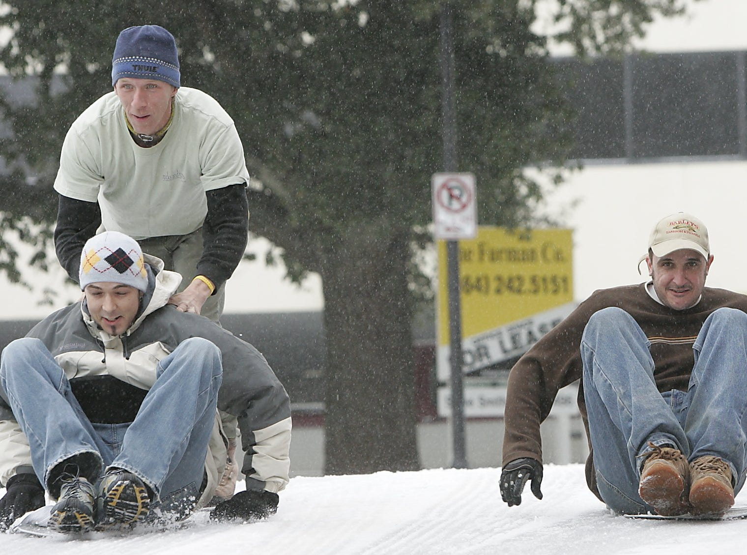 Barley's Taproom and Pizzeria employees, Zack Trotter, right, and Drew Moren take a break from work to slide down Laurens Street on pizza pans with Moren getting a little push from Brian Kettler, Saturday, January 29, 2005.