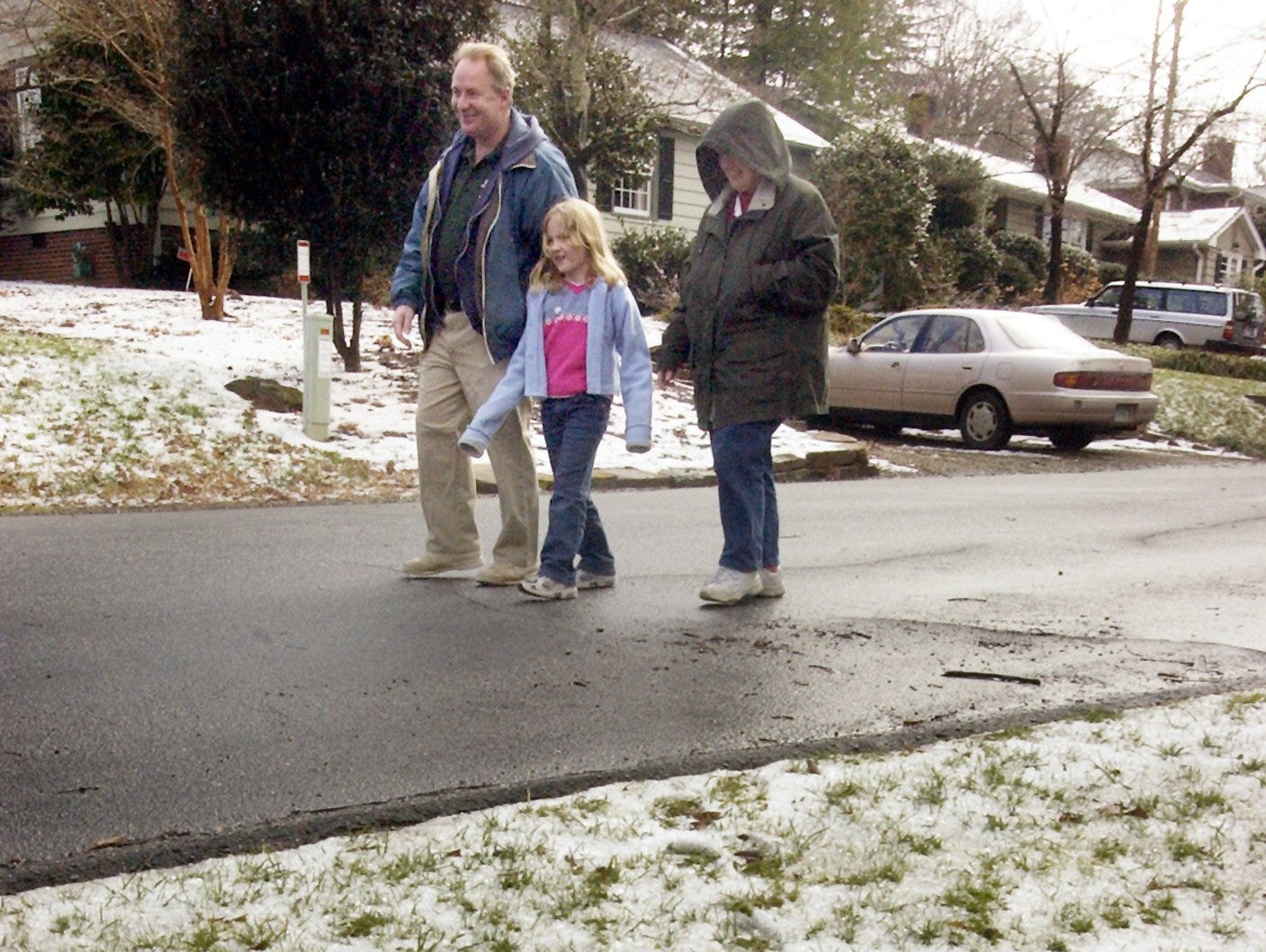 Madeline and Parrish Fletcher and their daughter Madeline, 6, enjoy a walk past the remants of snow in their Vista Hills neighborhood Sunday January 30, 2005.