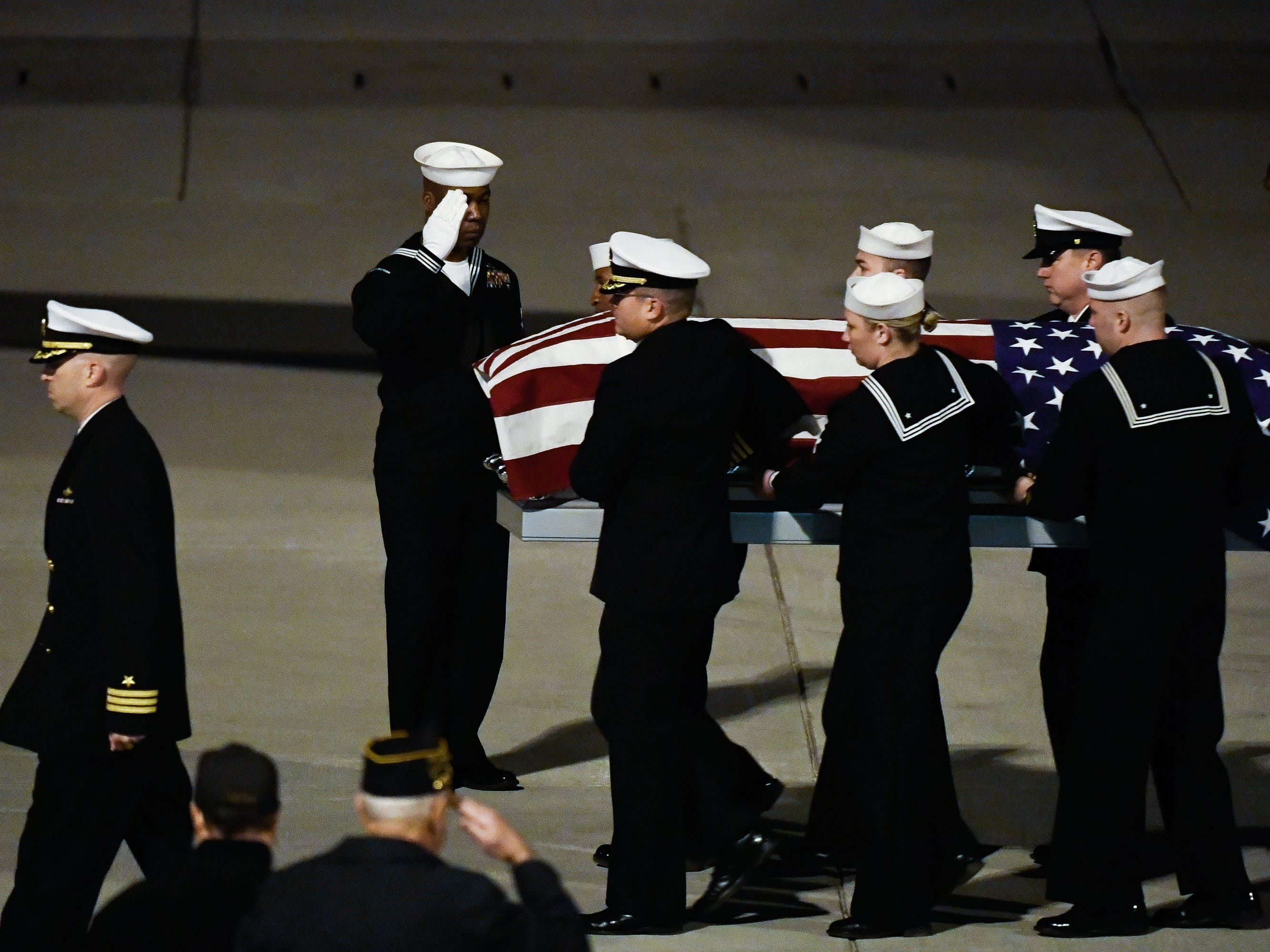U.S. Navy Fireman 2nd Class Carl Dorr is escorted off a Delta Airlines flight and brought home on Wednesday, Dec. 5, 2018 after his remains were identified through DNA evidence nearly 77 years after his death.