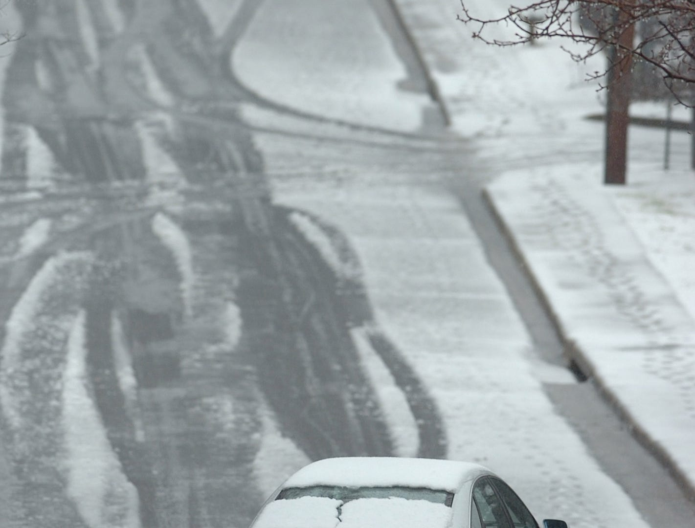 A car is driven down a snow covered Thruston St in downtown Greenville Thursday, February 1, 2007.
