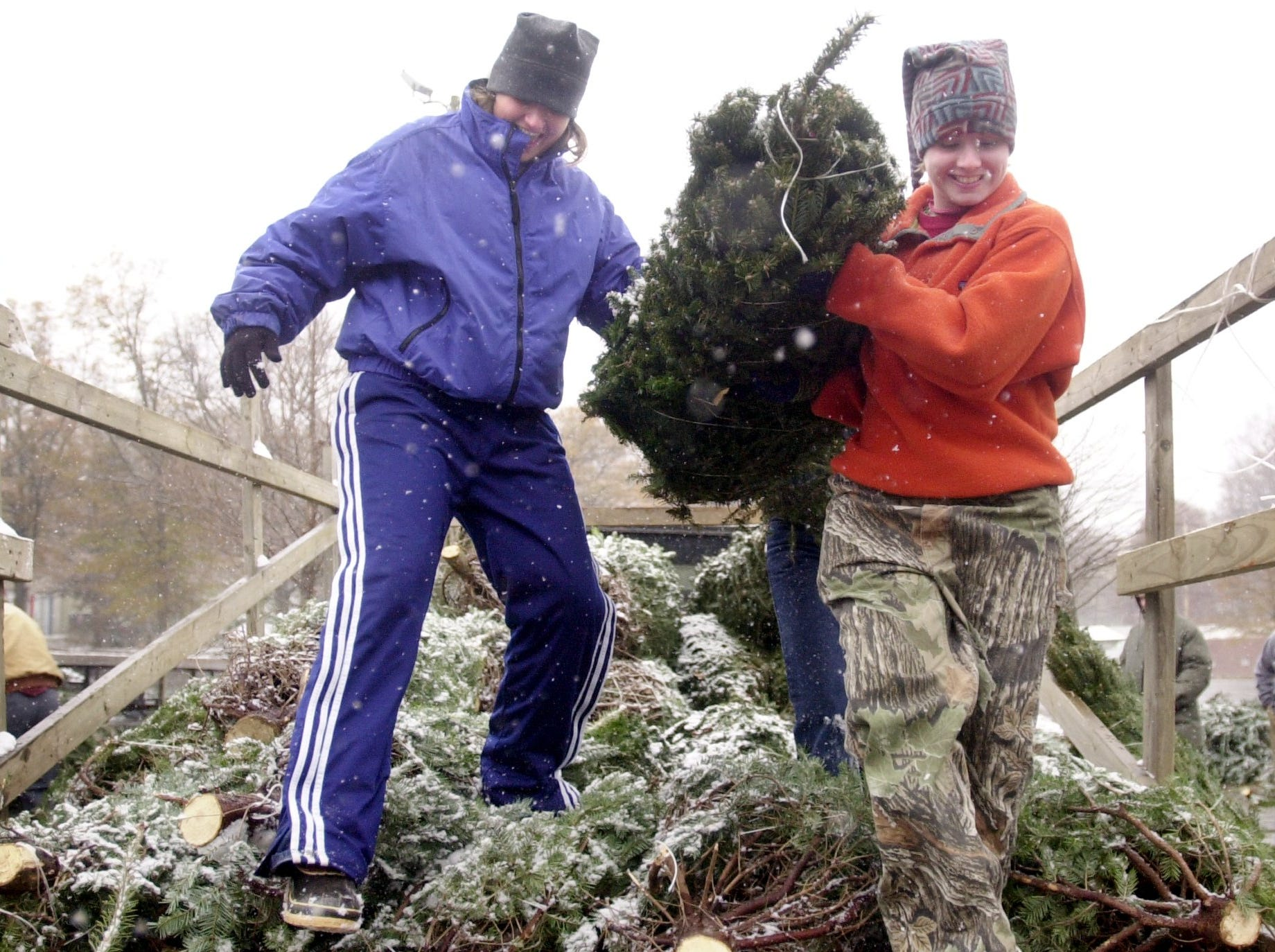 Greenville High School seniors Sarah Bishop,17 and Krissie Barr,17 unloaded Christmas trees at Sirrine Stadium for a fundraiser Sunday morning in the snow December 3, 2000.