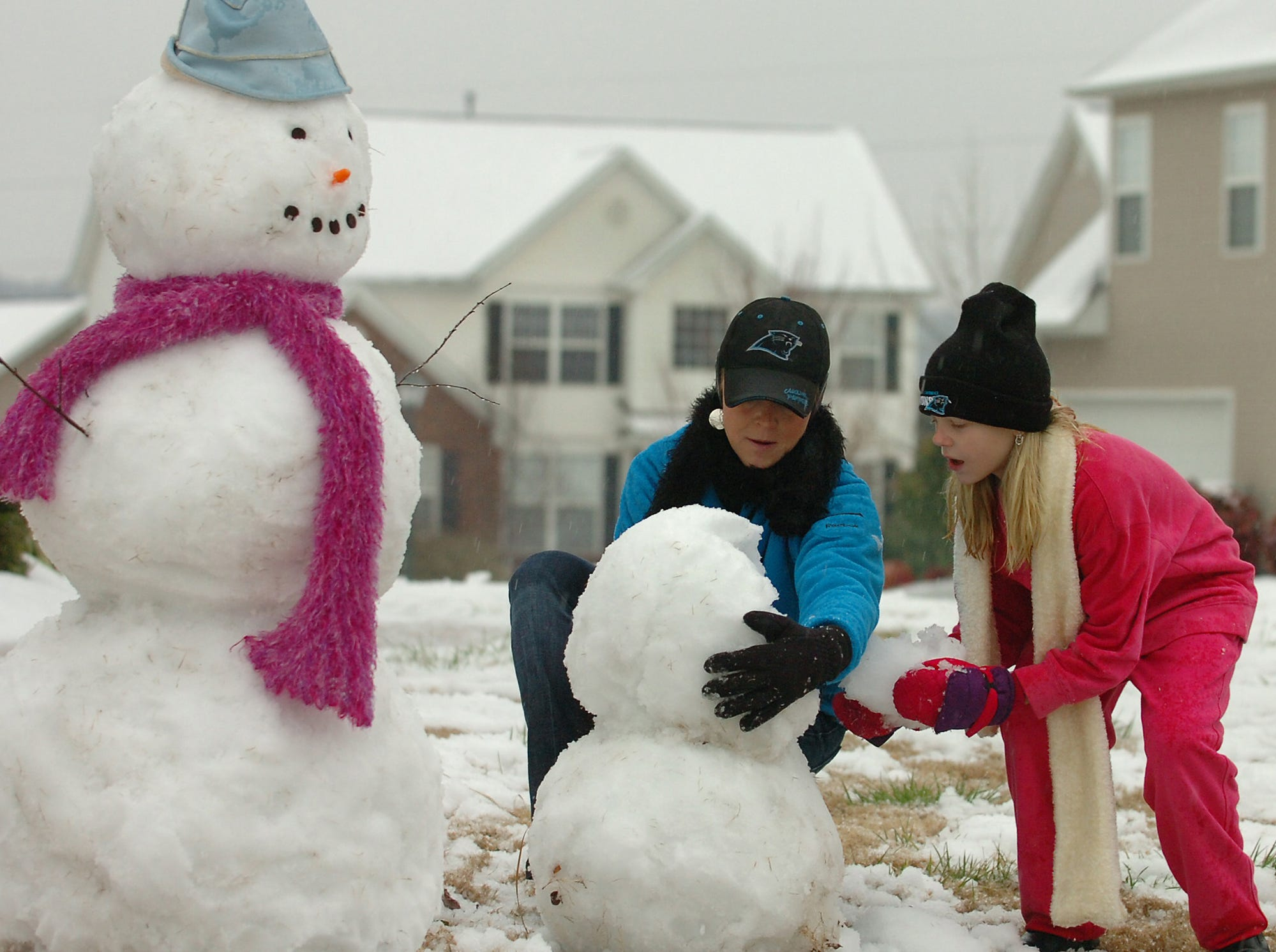 Tina Price and her daughter Brittany, 10, take advantage of the early snow and make a snow family in the front yard of their Mauldin home Thursday, February 1, 2007.