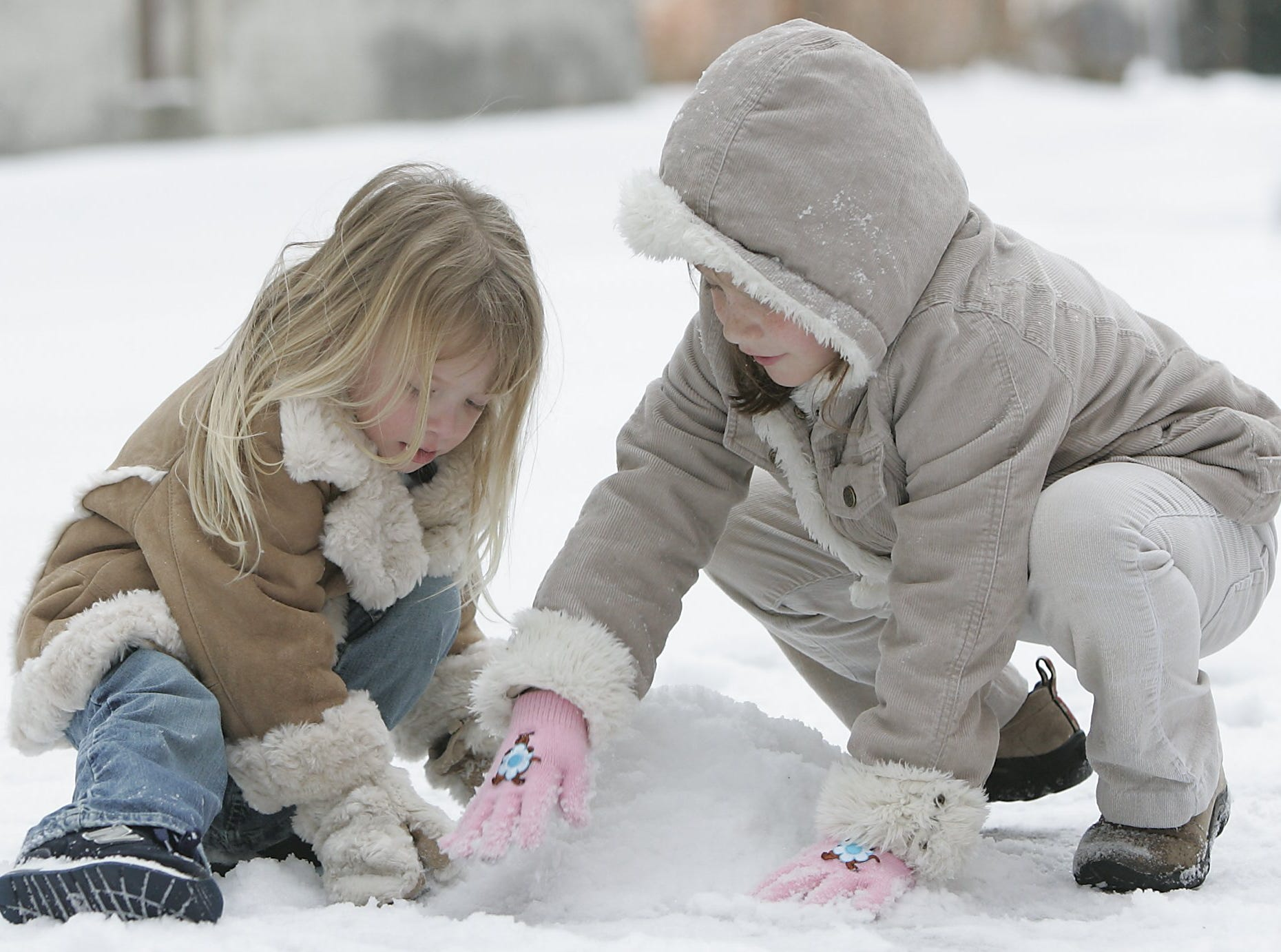-Macy Robert, 3, left, and Samantha DuPree, 6, of Charleston, start to make a snowman in downtown Greenville, Saturday, January 29, 2005.
