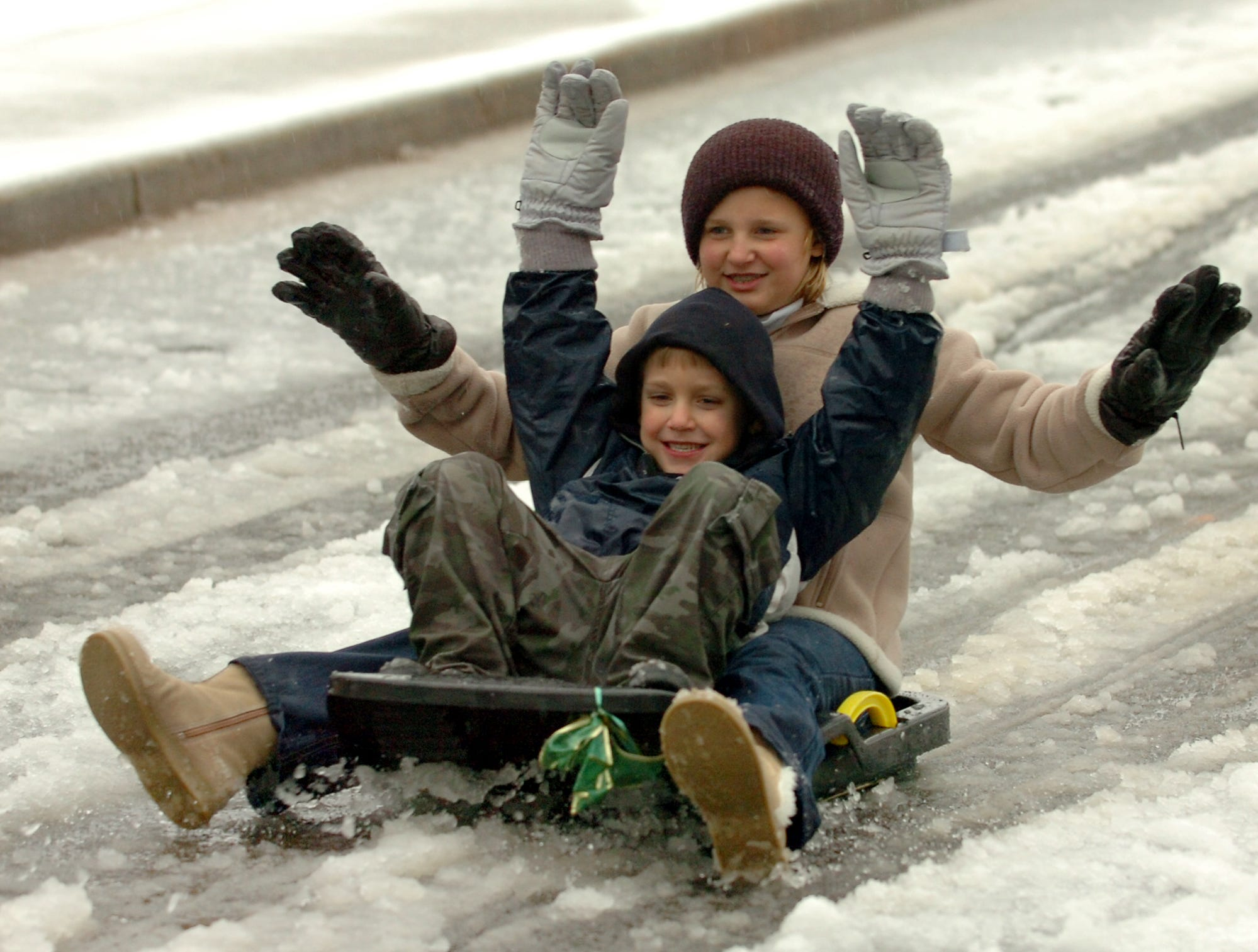 Megan Blume, 10, and her brother William, 6, enjoy sledding in Avondale Heights Thursday morning.