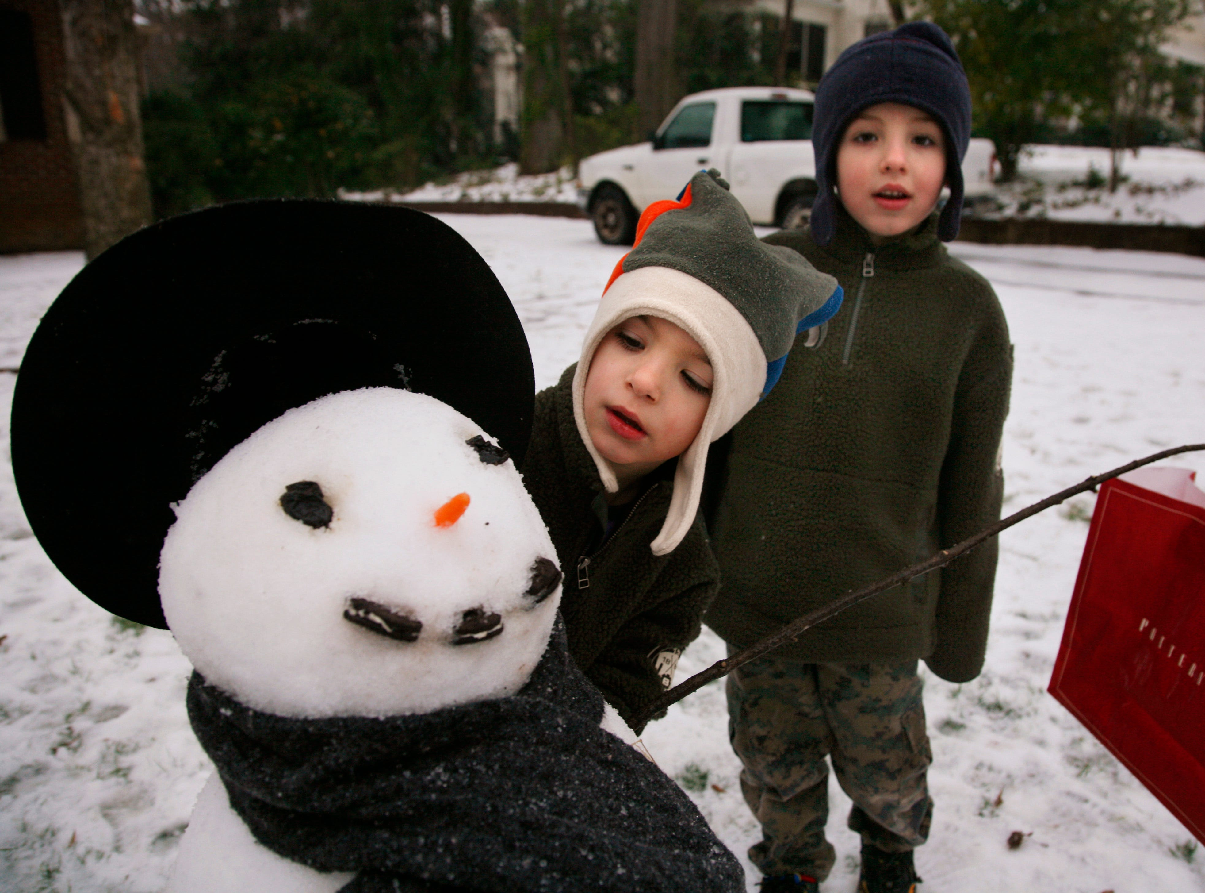 Craven Sykes, 4, and his brother Barber Sykes, 6, play with their snowman in front of their North Main Street home Thursday morning. Snow and rain blanketed Greenville Thursday, February 1, 2007.