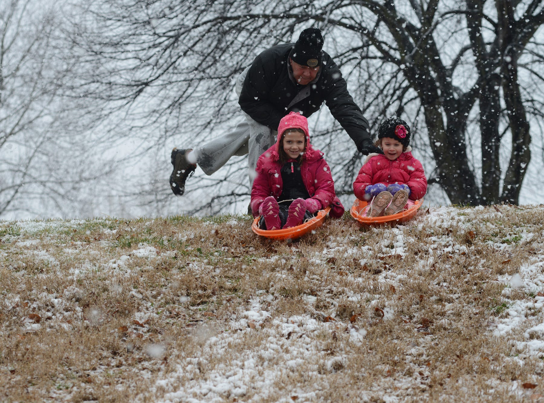 Gene Brees plays in the snow with his grandchildren McKinley Griffeth, left, and Lucy Griffeth, right, on the campus of Greenville Technical College on Tuesday, February 11, 2014.