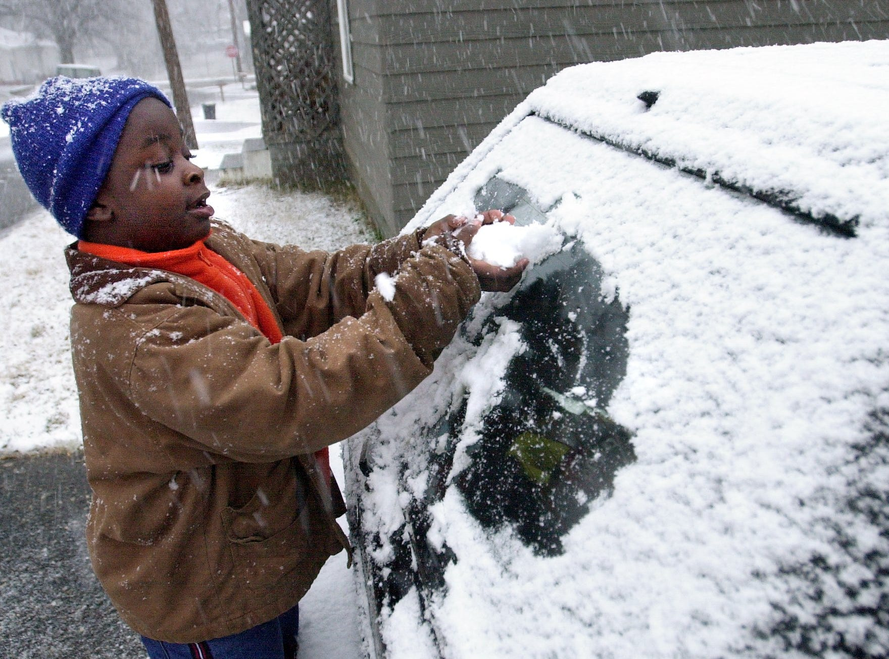 Bradley Brooks, 5, gathers snow from a car near his home on Holiday St. in Greenville as snow falls Thursday January 16, 2003.
