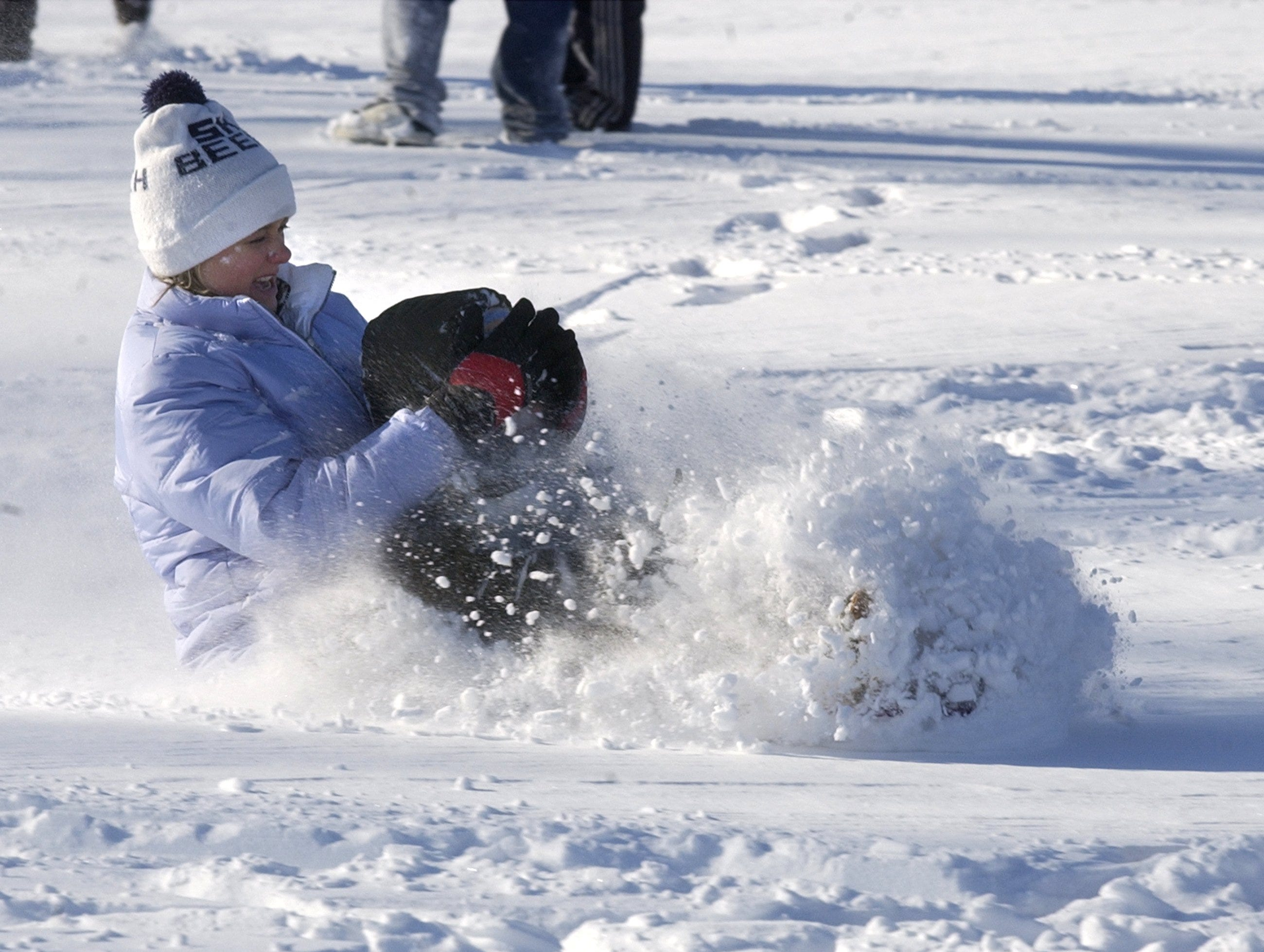Pam Bass shields her son Parker from a snow coming off a sled ride at Holly Tree golf course January 23, 2003.