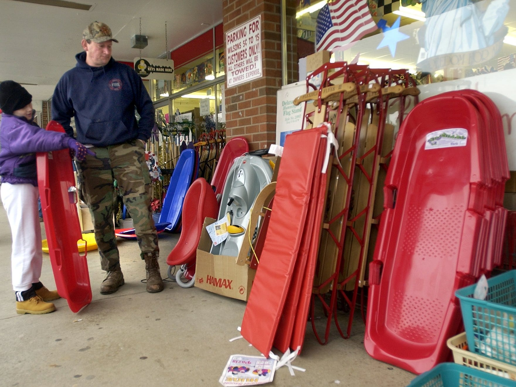 Danielle Waynick, 9, and her father Tommy Waynick shop for sleds at the Wilson's Five and Dime in Berea Wednesday afternoon. Waynick said they live in Travellers Rest which was getting some snow while they shopped. Store manager Jane Jobe said she's shold close to 100 sleds adn gotten calls from as many shoppers asking if they had sleds.