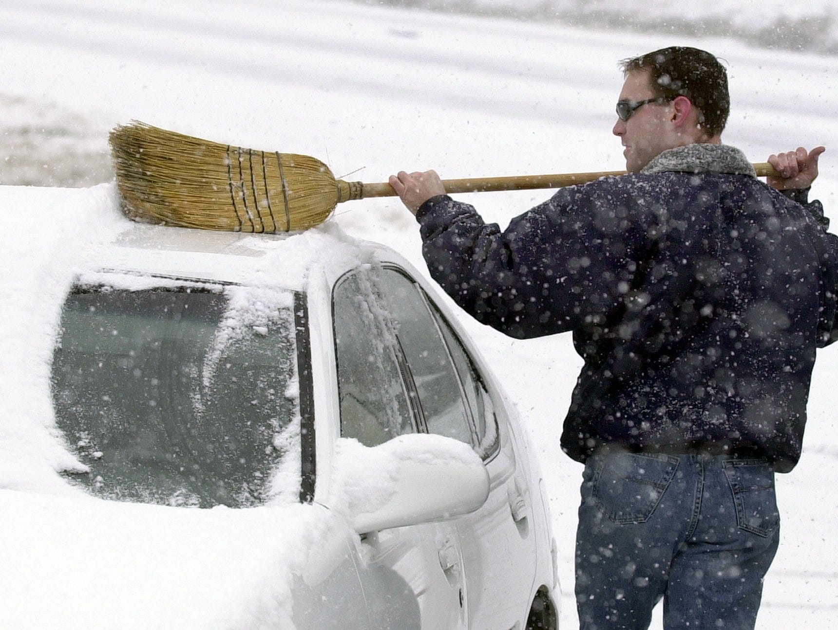 Jeff Hull with Thrifty Car Rental on Poinsett Hgwy makes a clean sweep of snow from one of the cars on his lot January 3, 2002.